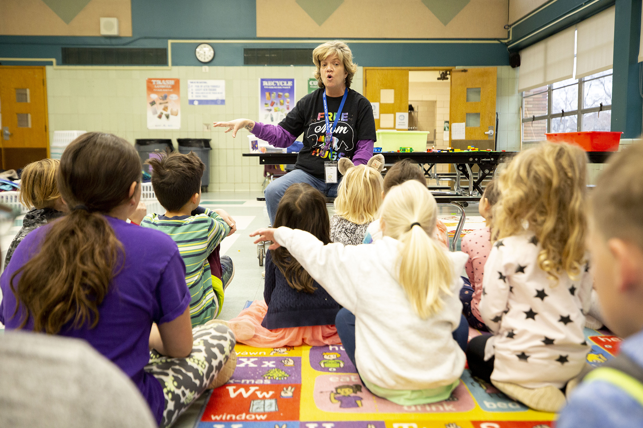 An after-school program supervisor talks to children seated on a classroom rug.