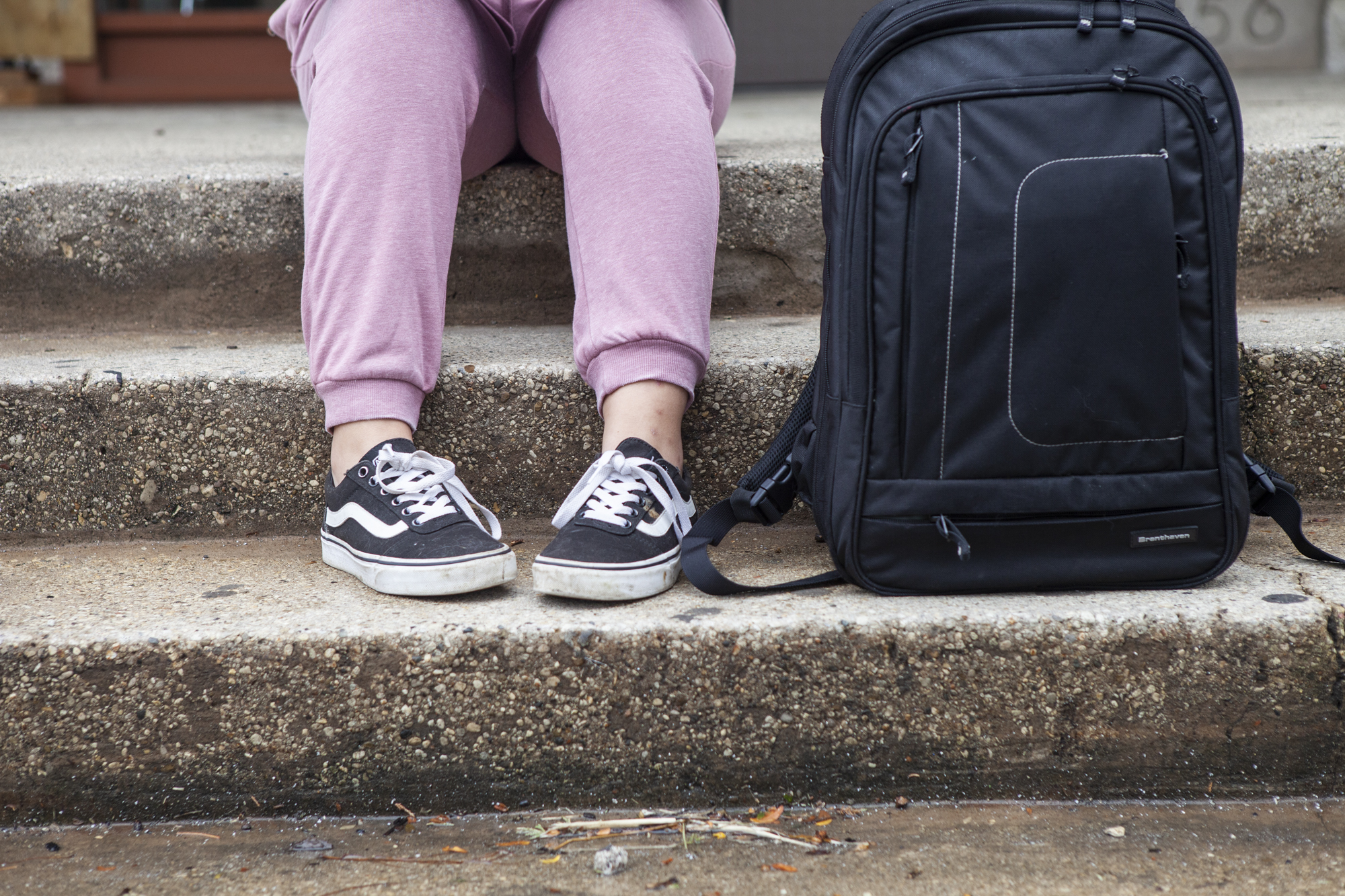 Close-up of a students sneaker's and backpack on steps outside school.
