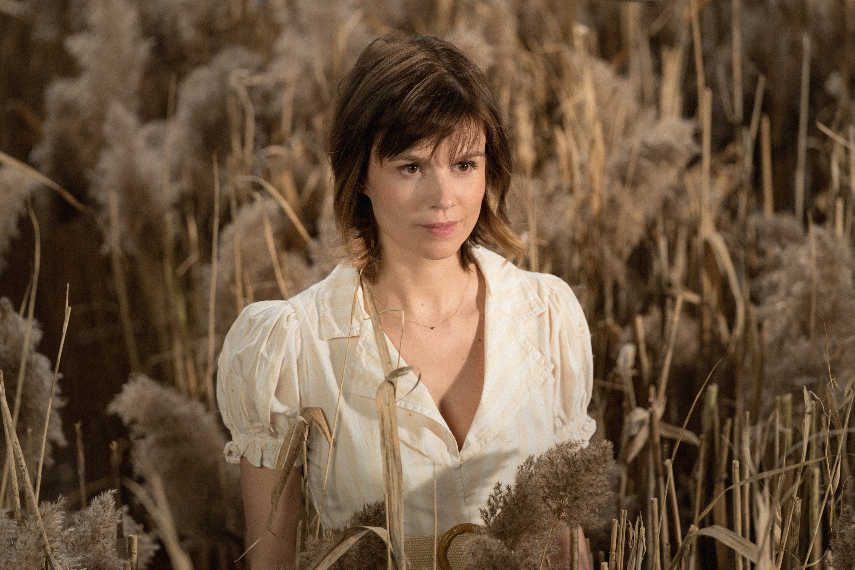 Katja Herbers as Kristen Bouchard standing in a wheat field during a dream sequence in Evil
