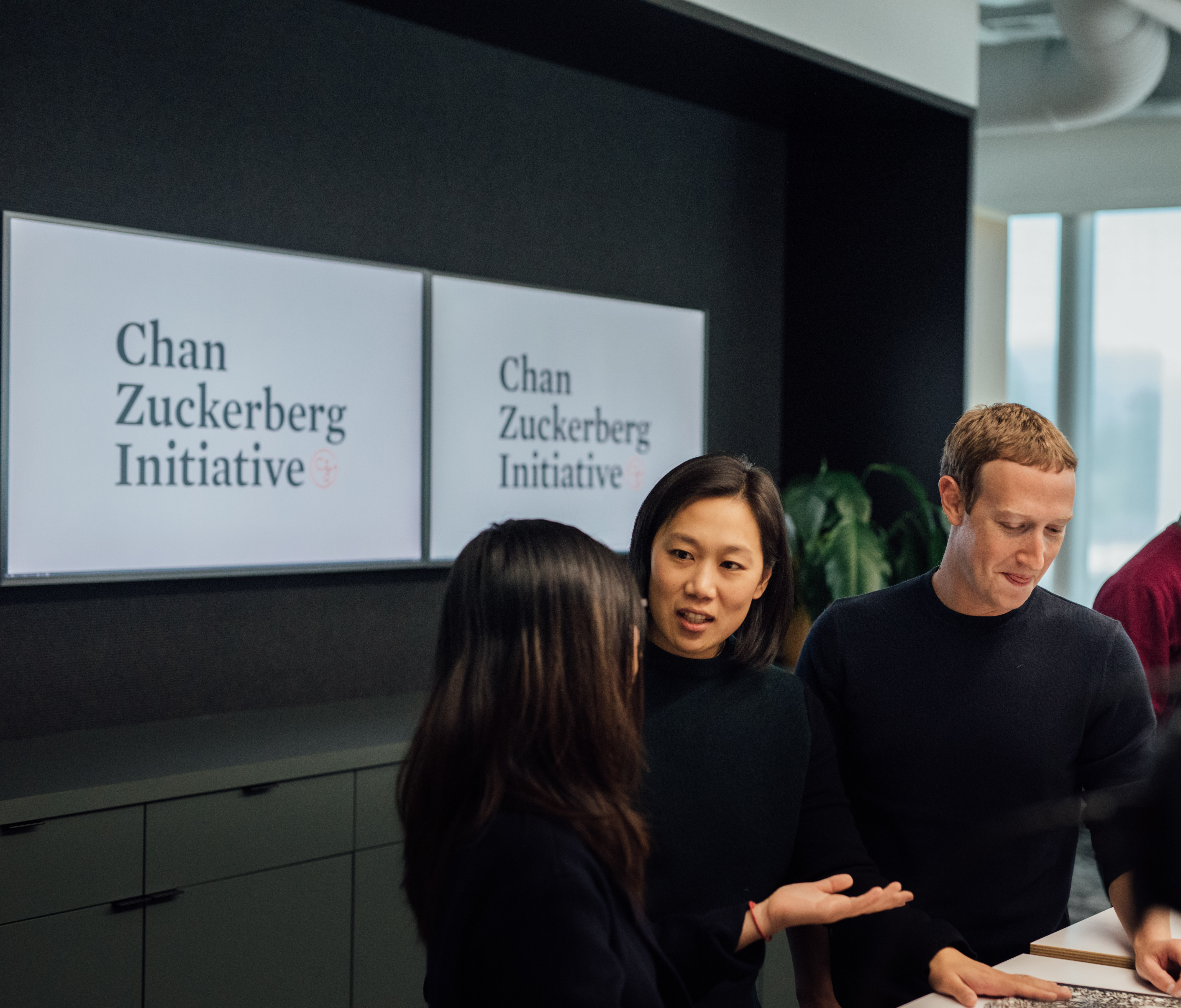 """Priscilla Chan and Mark Zuckerberg speak with another person in front of a sign reading, """"Chan Zuckerberg Initiative."""""""