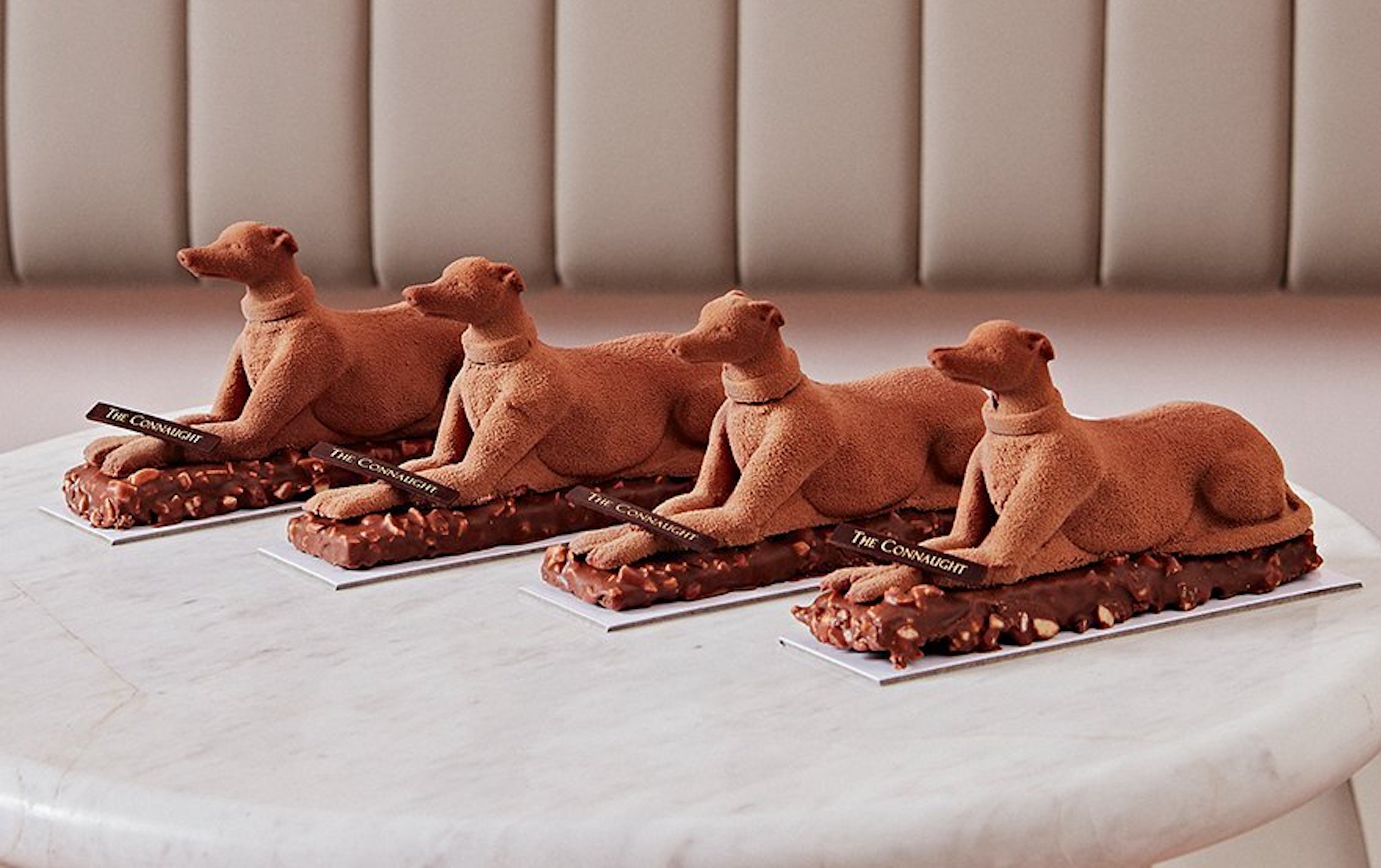 Four chocolate patisserie dogs sitting in a row on a marble effect tabletop