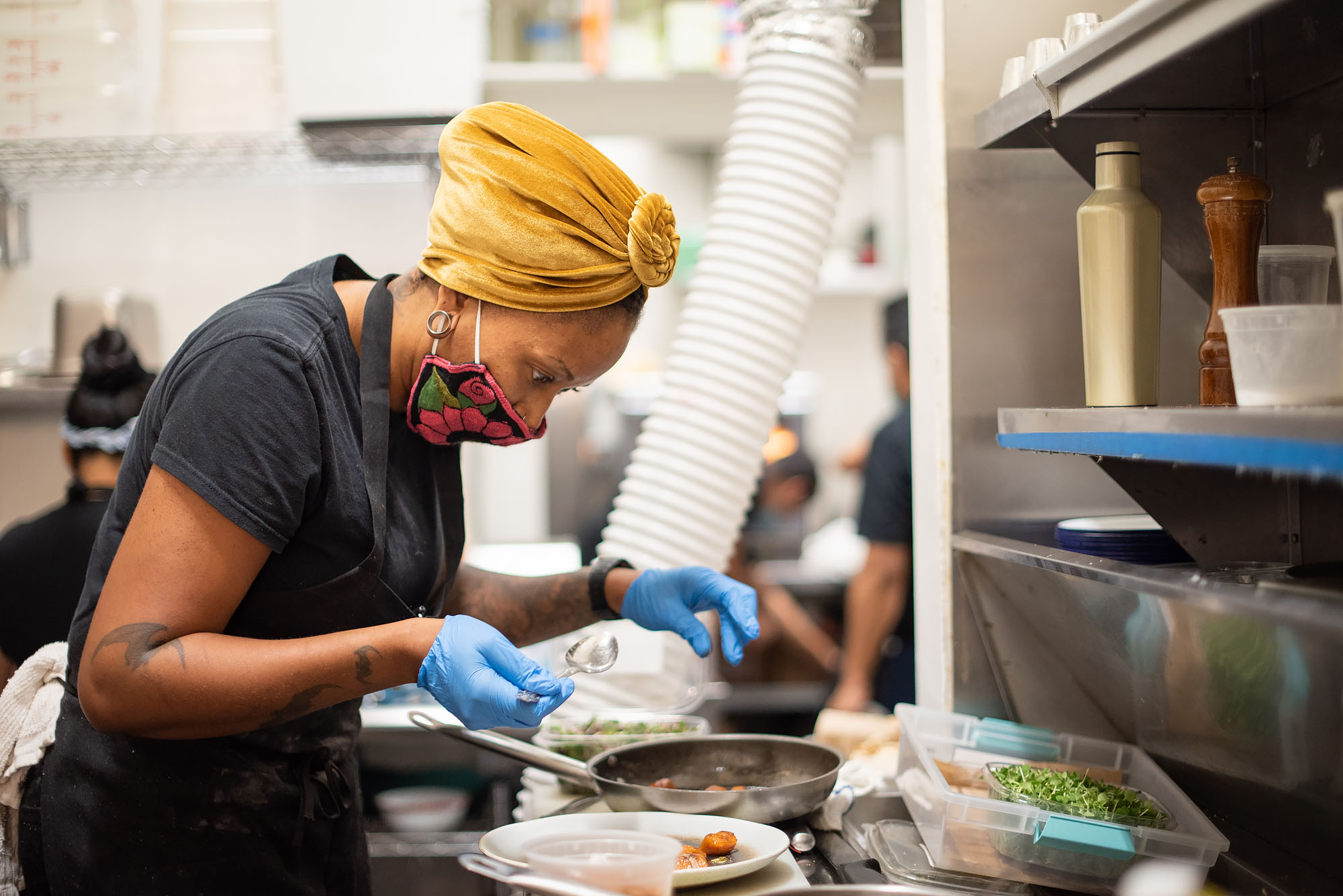 A female chef in yellow head scarf prepares a meal inside of a kitchen, while wearing a mask.