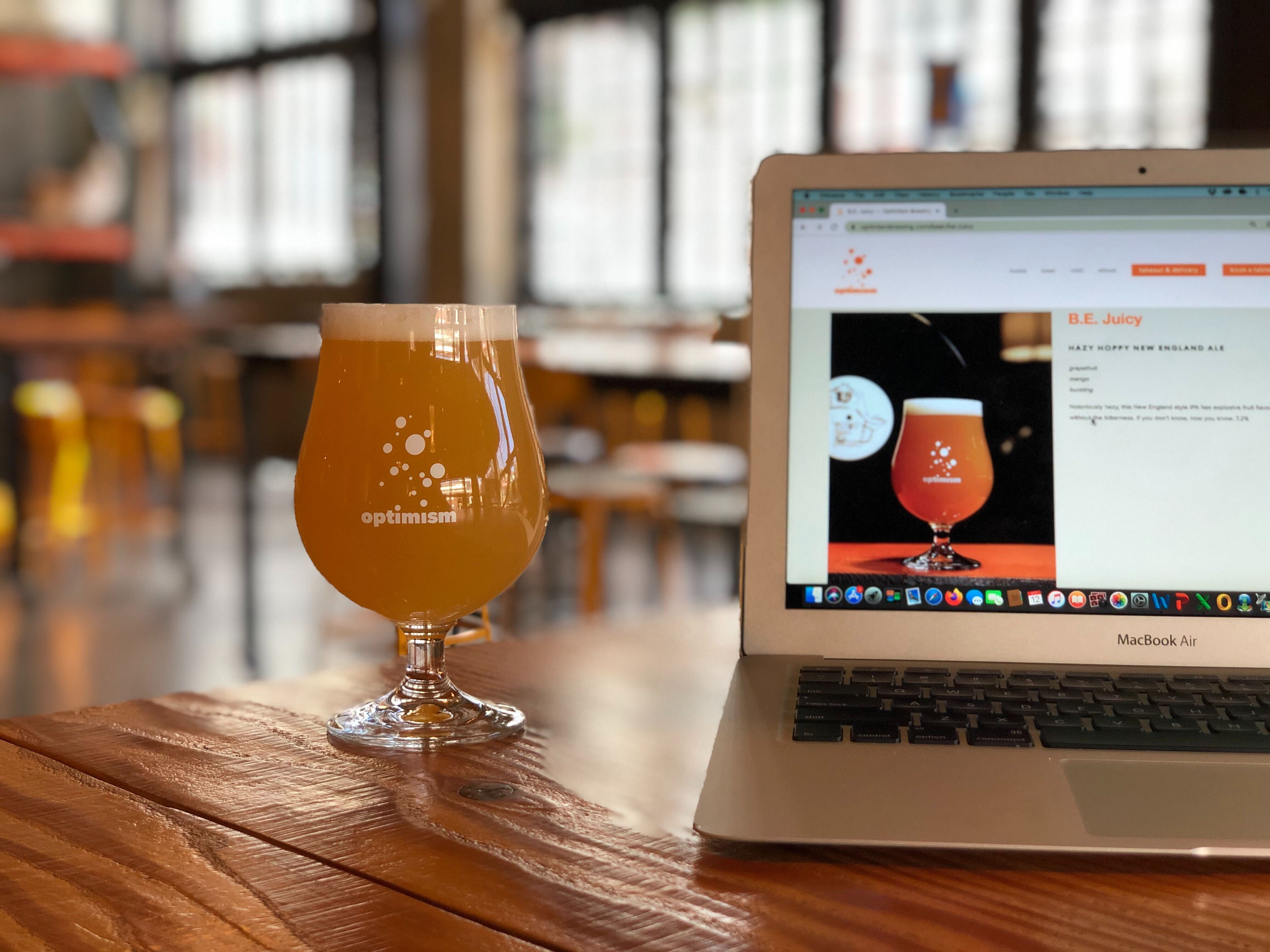 A glass of beer sits on a table at Optimism Brewing, with an open laptop that shows the name of the beer