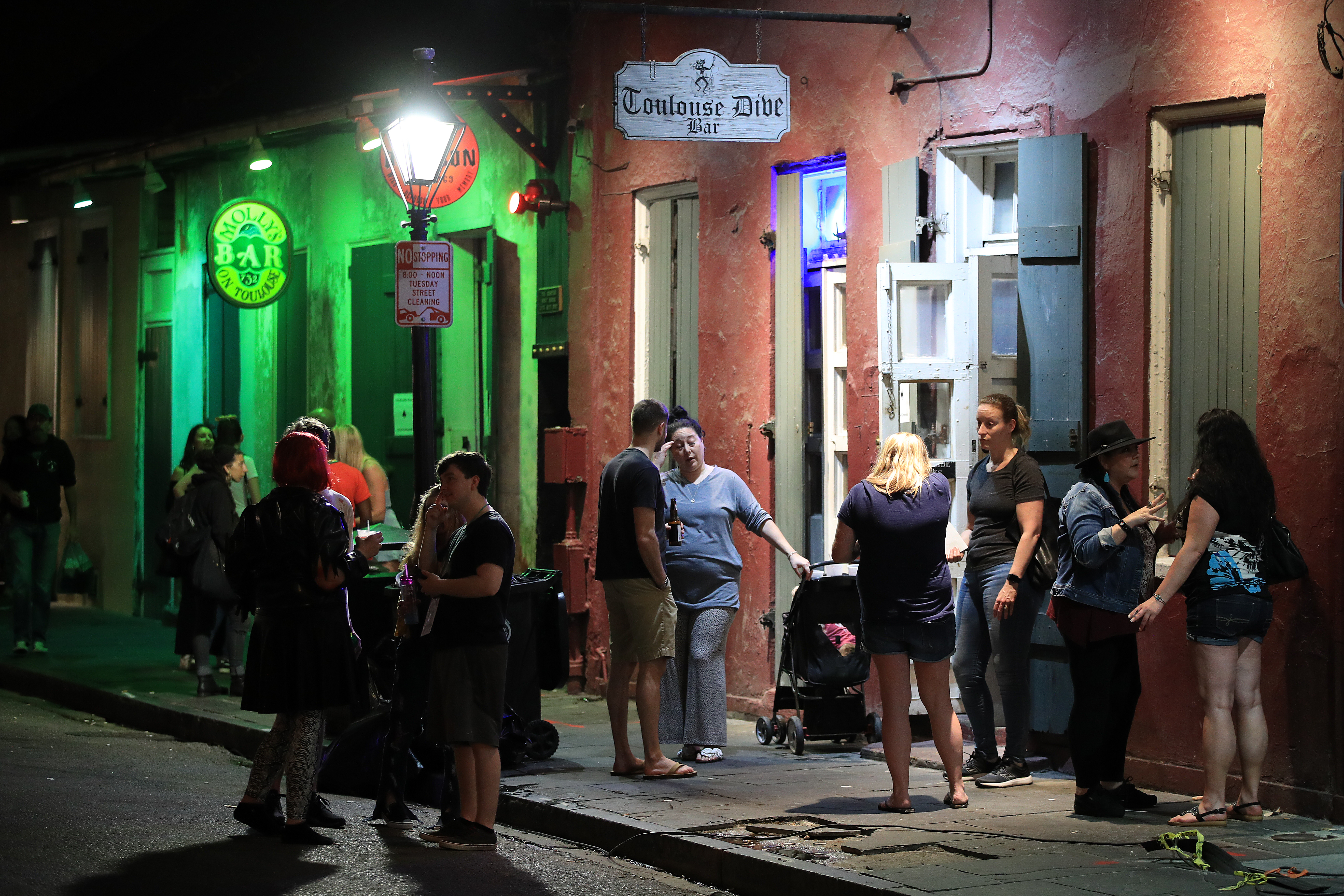 People stand in the street outside of a French Quarter bar on the night of March 16