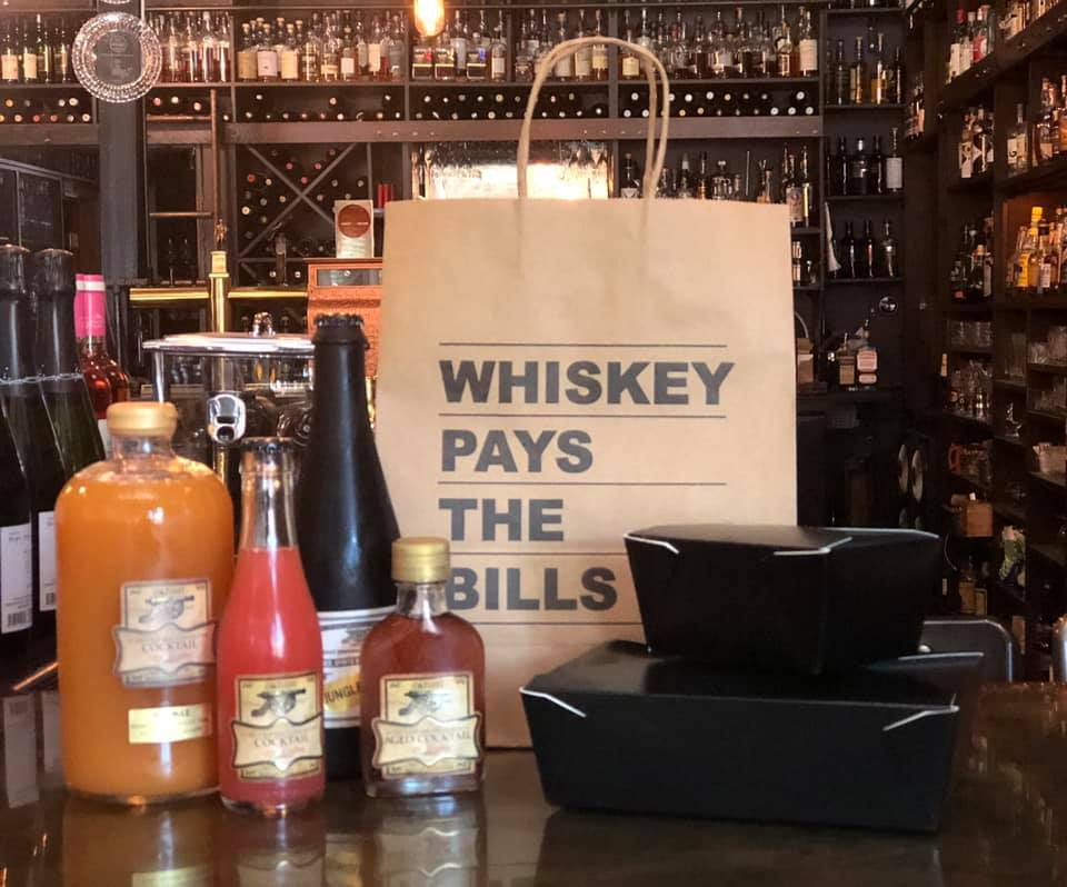 """A collection of bottled cocktails at Canon, with a large paper to-go bag that says """"Whiskey Pays the Bills"""""""