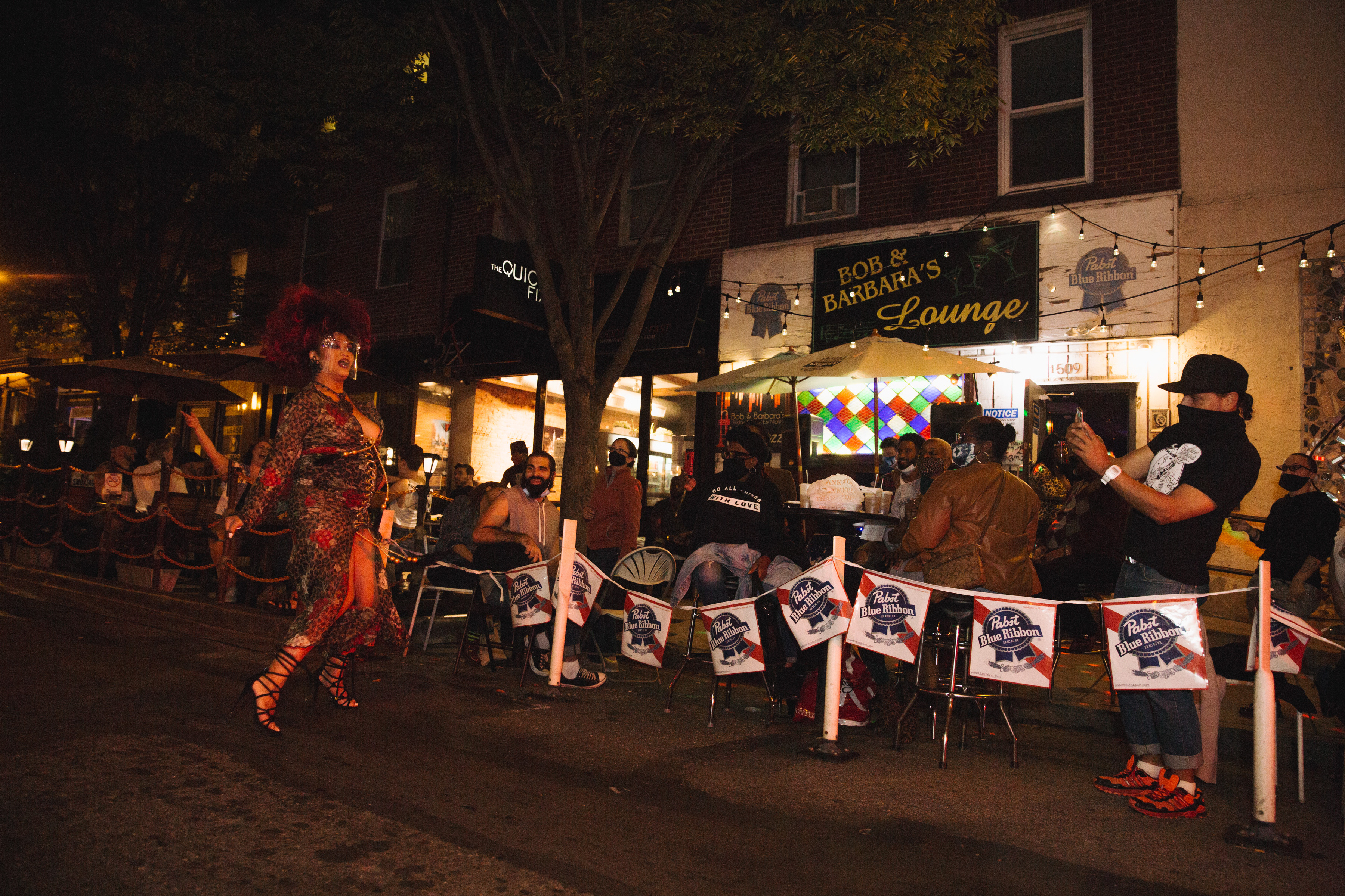 outside of dive bar with posts around tables holding pbr beer signs, a drag performer in the street, and a bar customer taking a photo