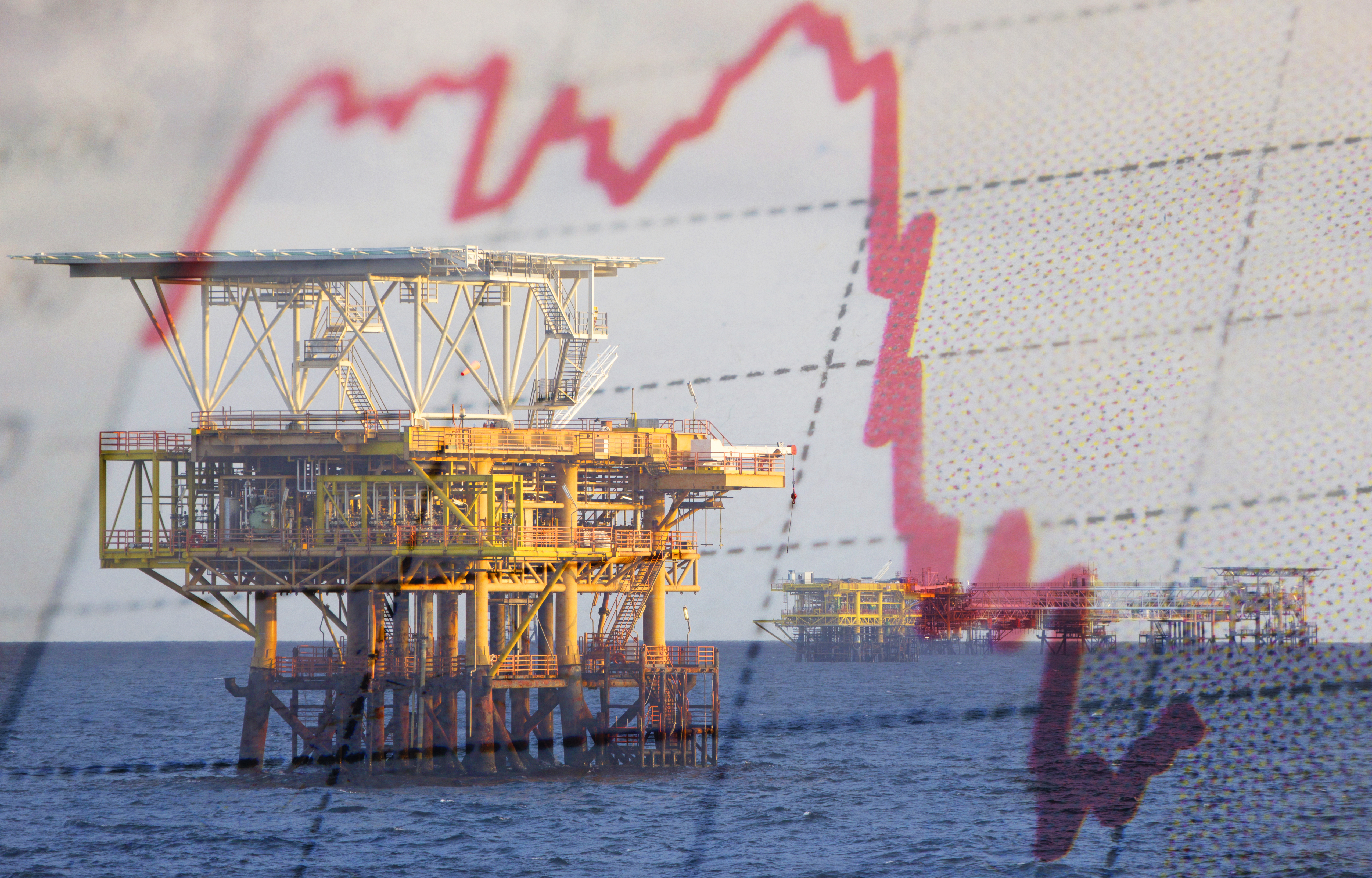 An oil rig in the ocean, seen in a reflection on a chart.
