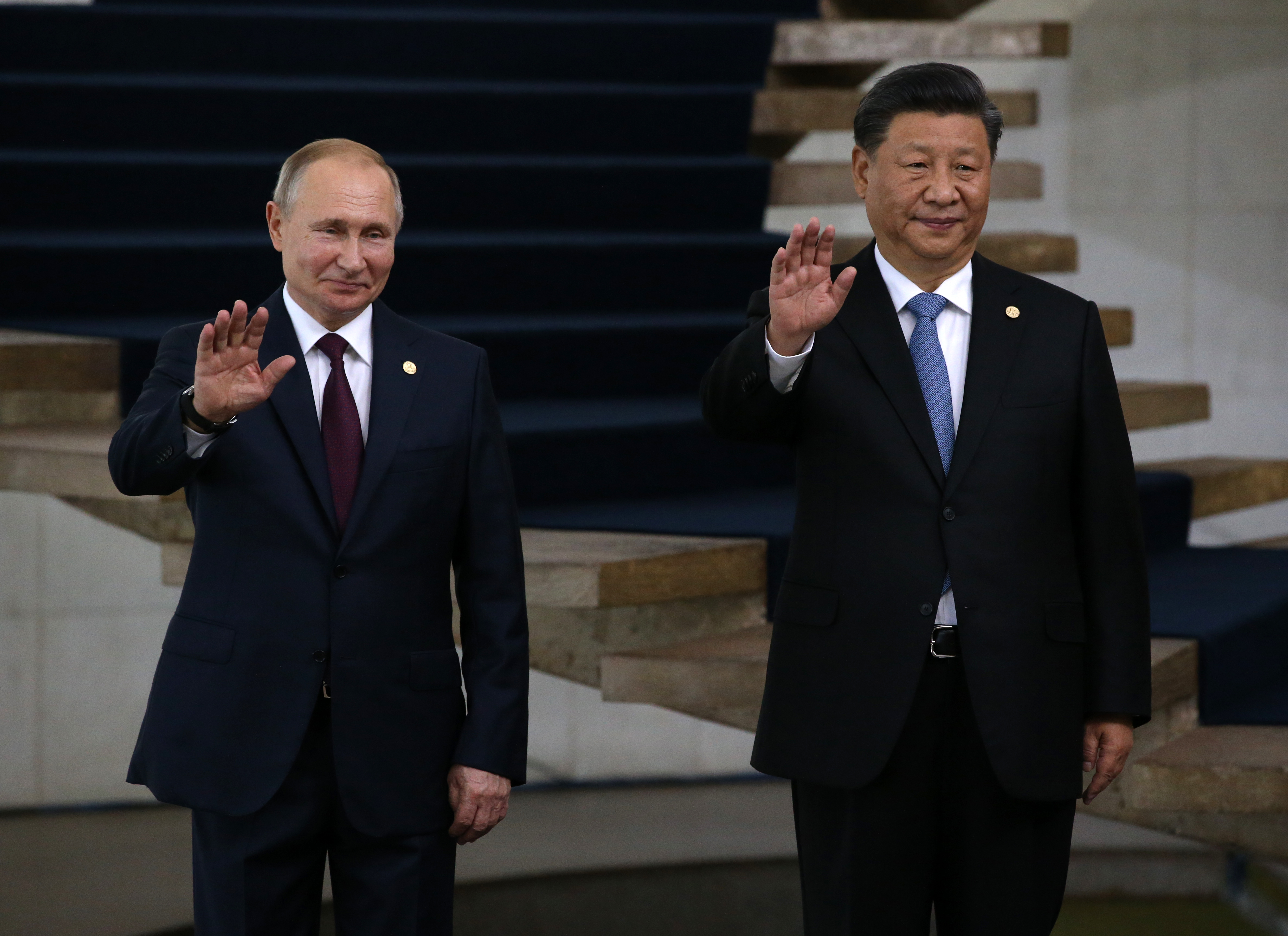 Russian President Vladimir Putin and Chinese President Xi Jinping smile and wave
