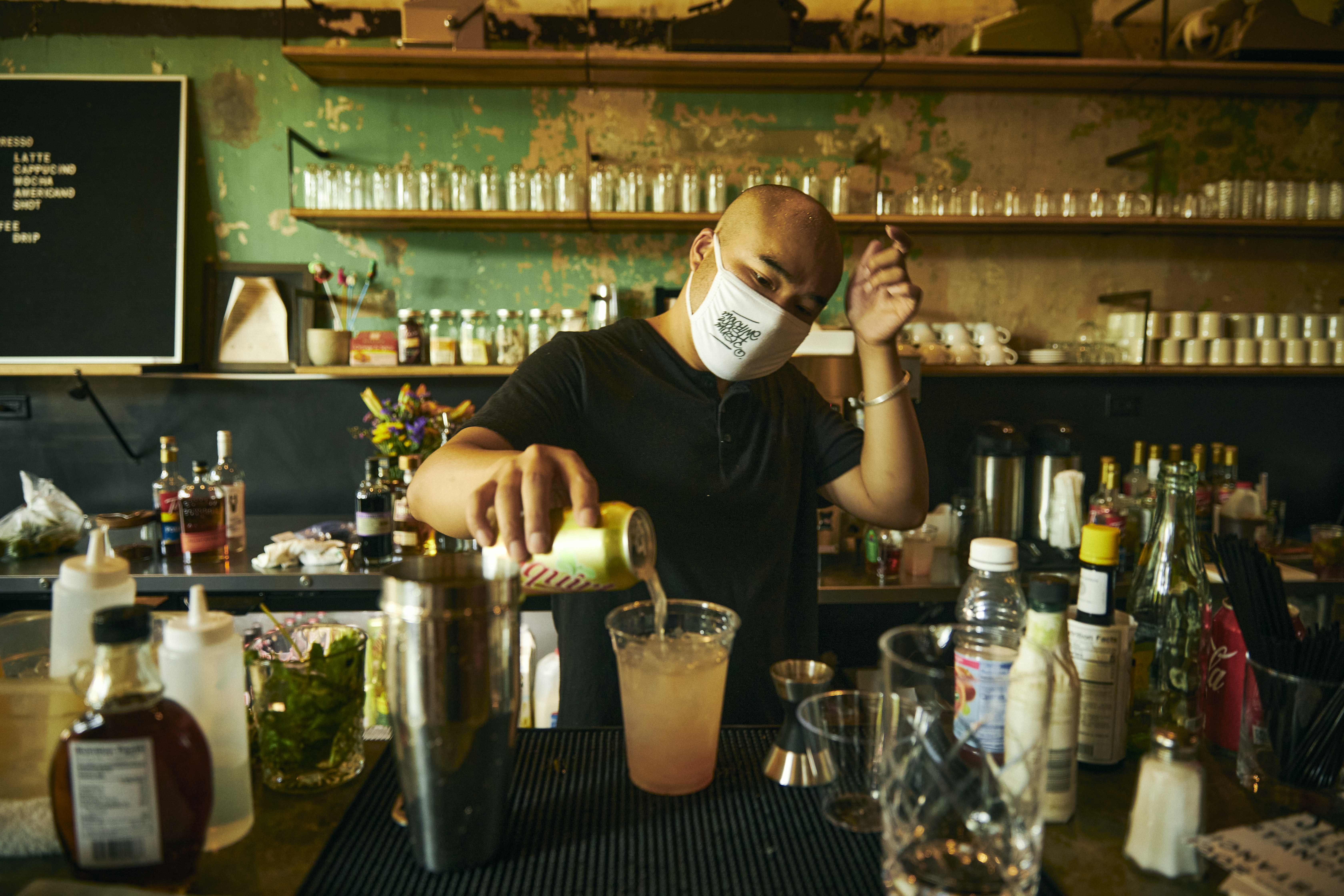 A person with a shaved head and a face mask pours a cocktail from a metal shaker into a plastic cup.