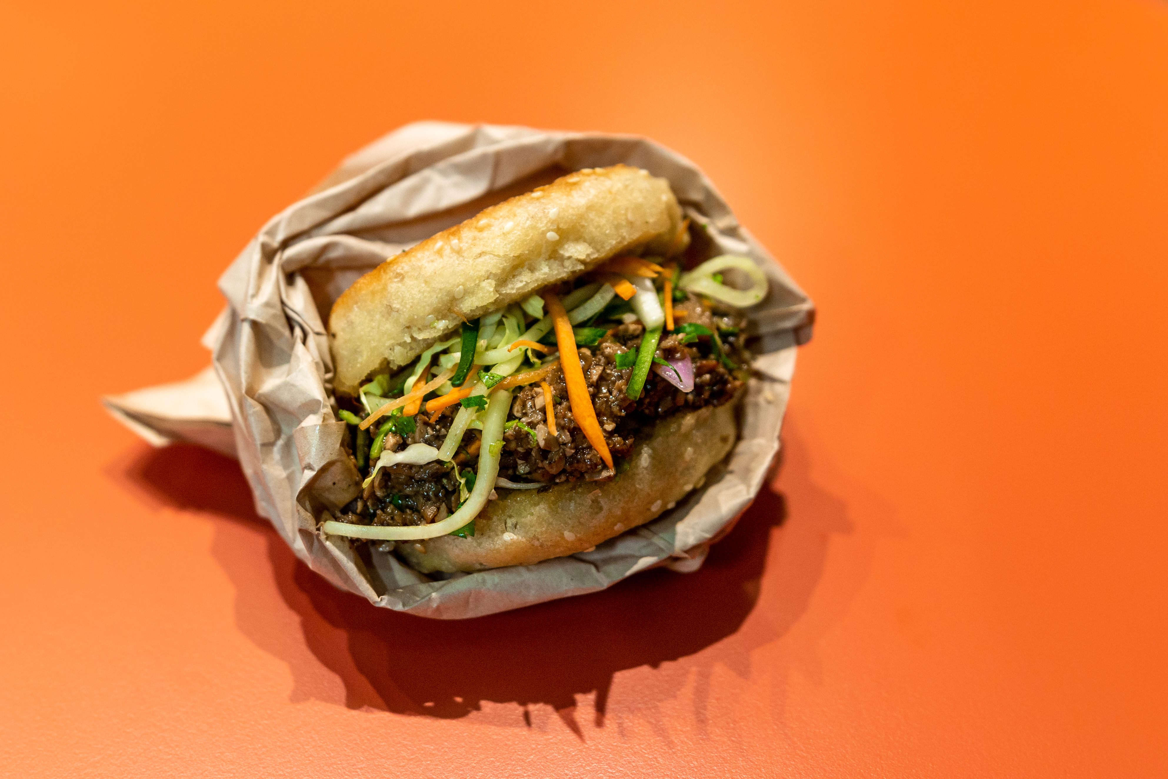 A sesame pancake sandwich in a takeout wrapper houses carrots, a mixture of darkened mushroom, and other accoutrements on an orange countertop