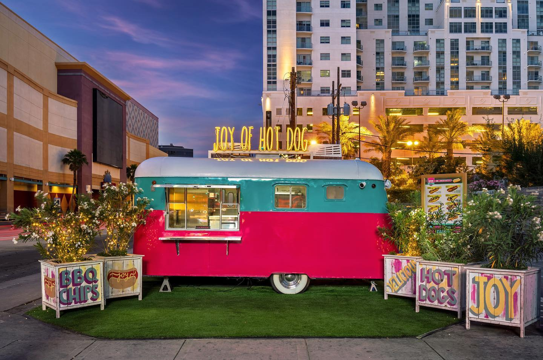 A neon lit, pink and aqua hot dog trailer