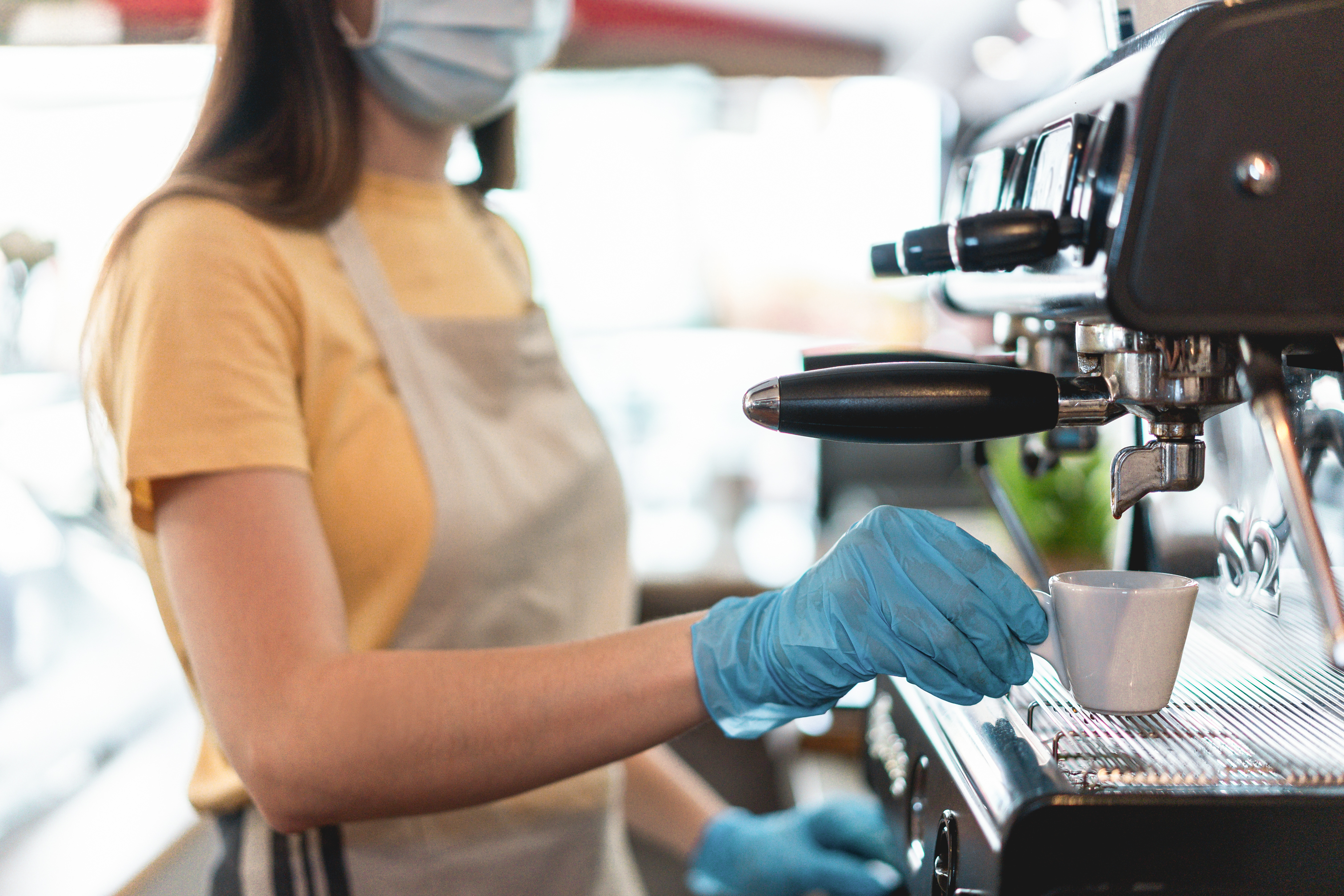 Young female working inside bar restaurant while making coffee wearing gloves and face mask for coronavirus spread prevention - Protective measures at work during Covid-19 outbreak - Focus on hand
