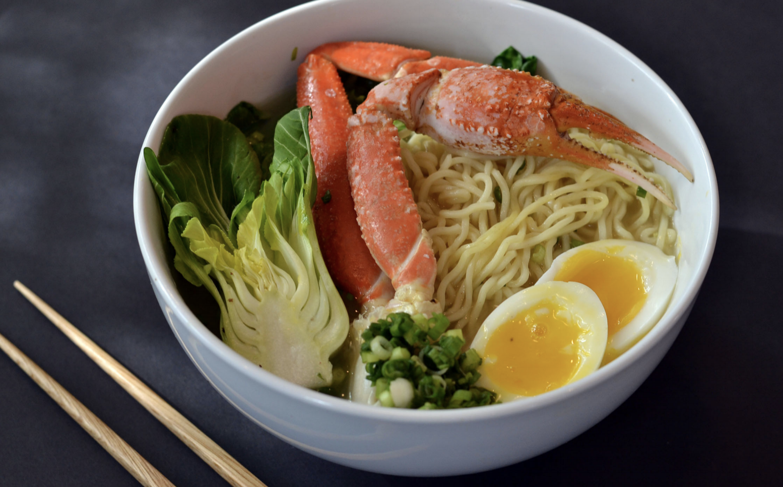 A view of a bowl of ramen with crab legs, hard boiled eggs, and cabbage, and chopsticks on the side