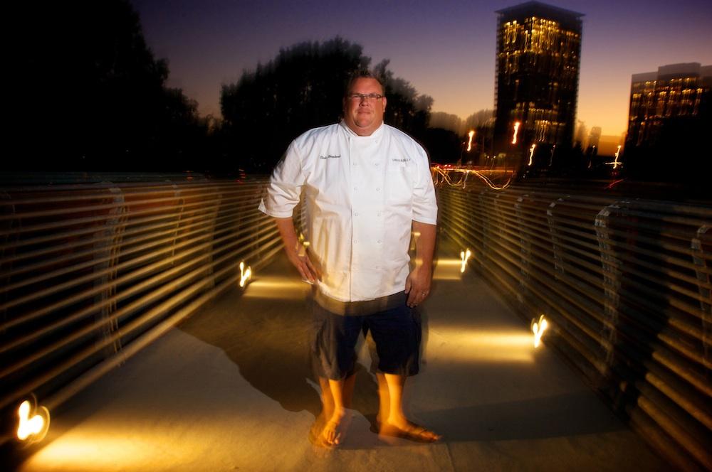 A man in galoshes stands on a pedestrian bridge