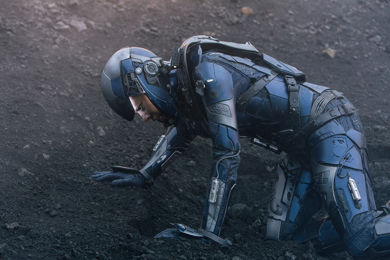 Sonequa Martin-Green as Michael Burnham lies in the dirt in her EVA armor in season 3 of Star Trek Discovery