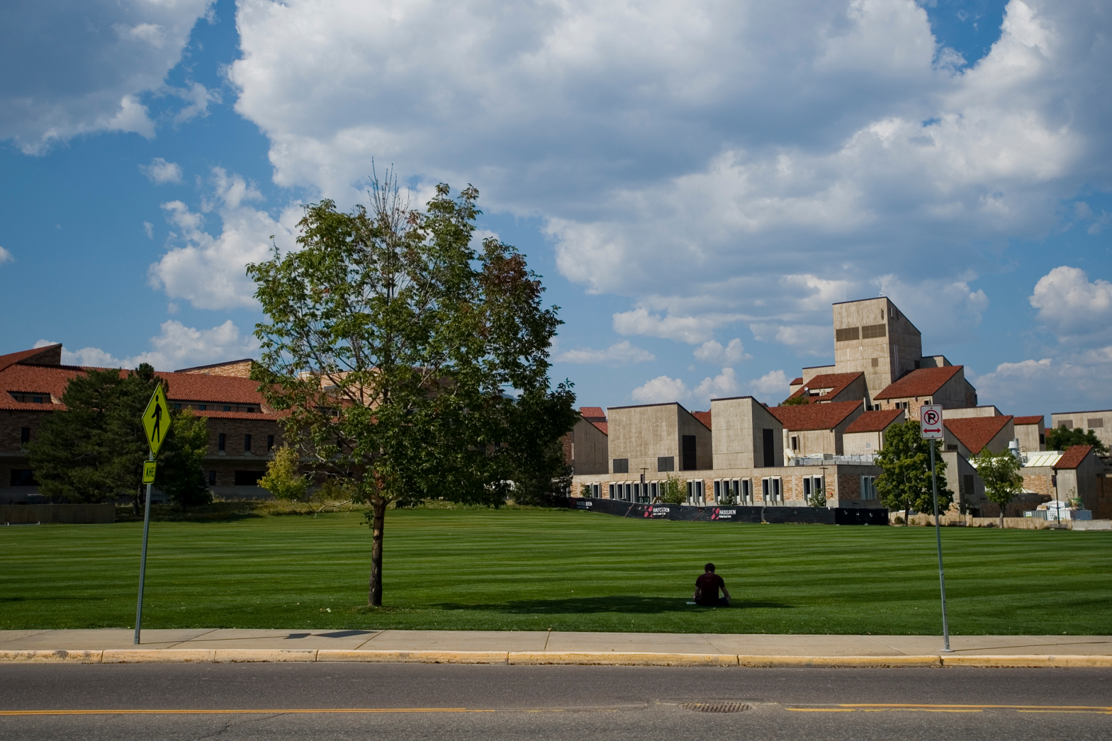 A University of Colorado Boulder student studies in the shade of a tree in front of Business Field with school buildings in the background.