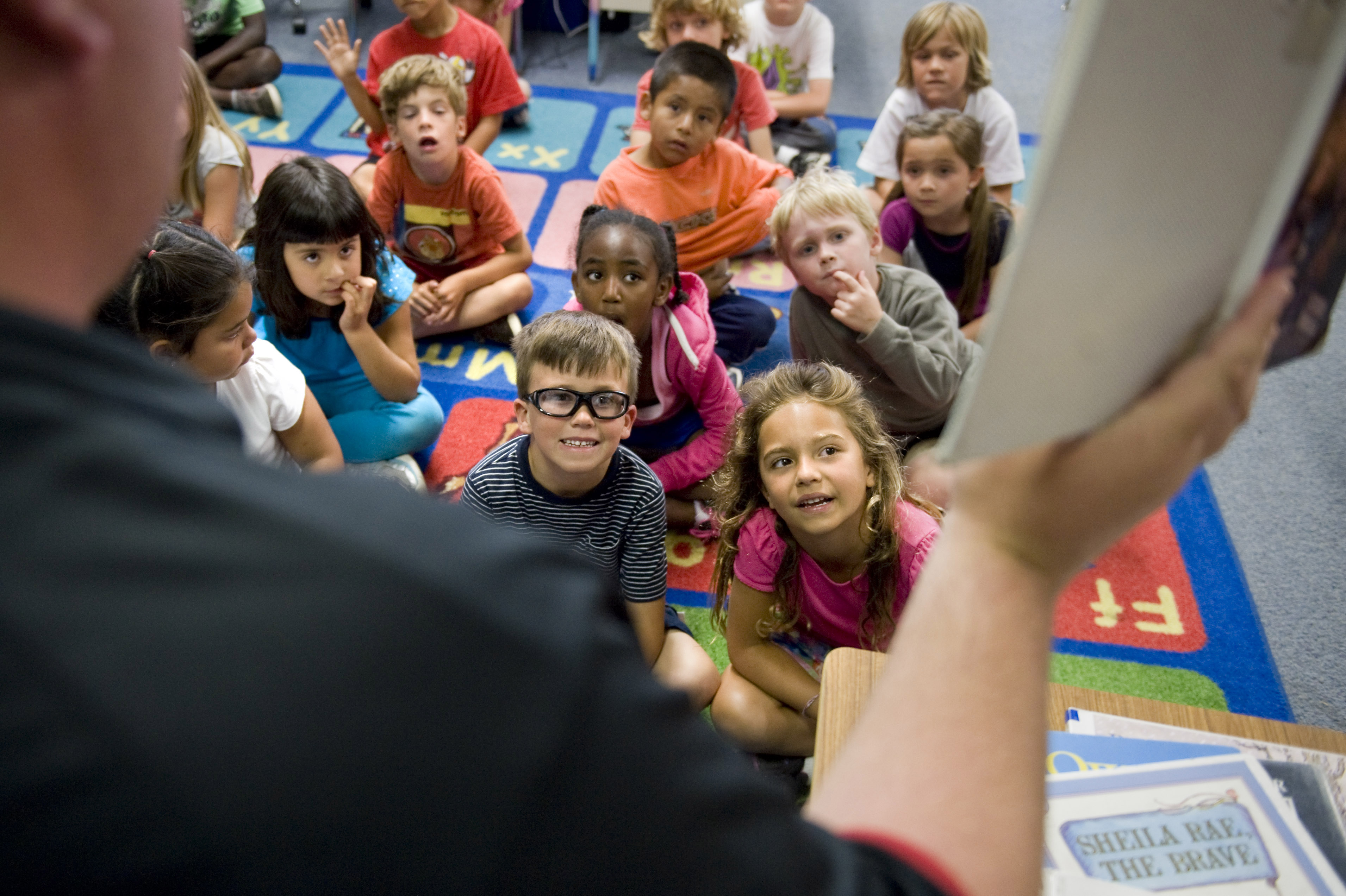 Young students sit on a carpet looking at a teacher holding part of a lesson