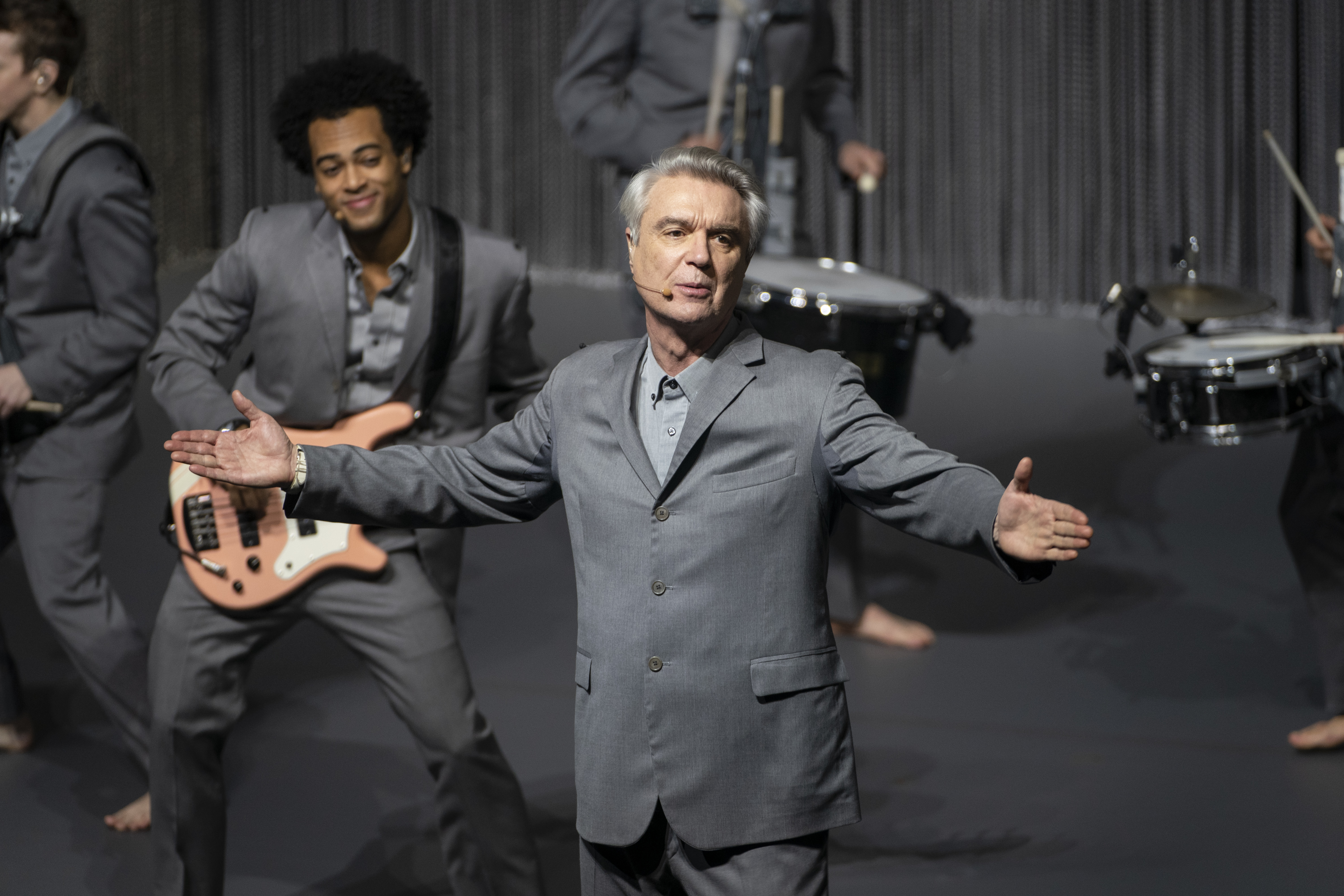 David Byrne, in a grey suit, stands with his hands spread out wide.
