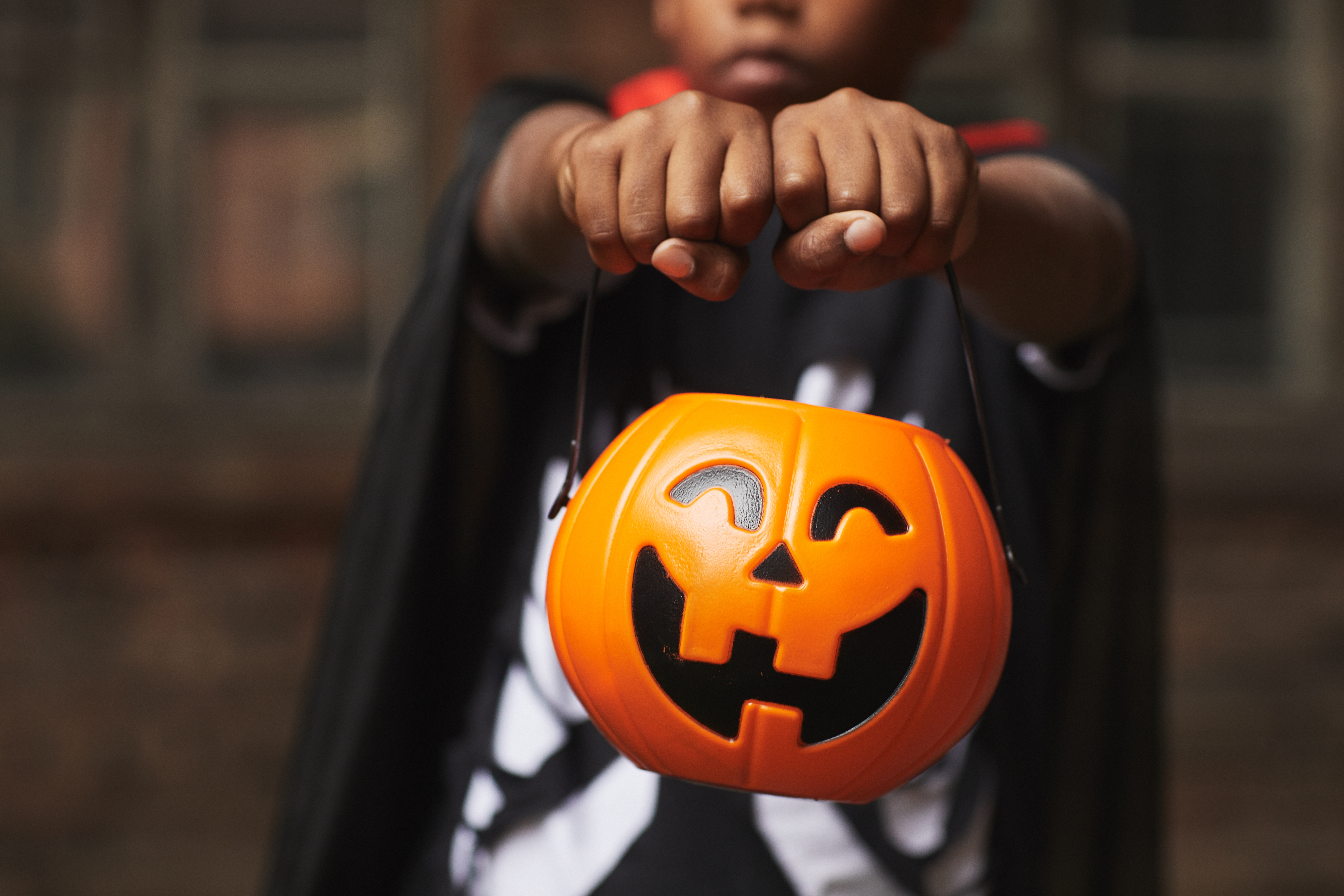 Unrecognizable boy wearing modern Halloween costume demonstrating plastic Jack O' Lantern basket for candies while trick-or-treating