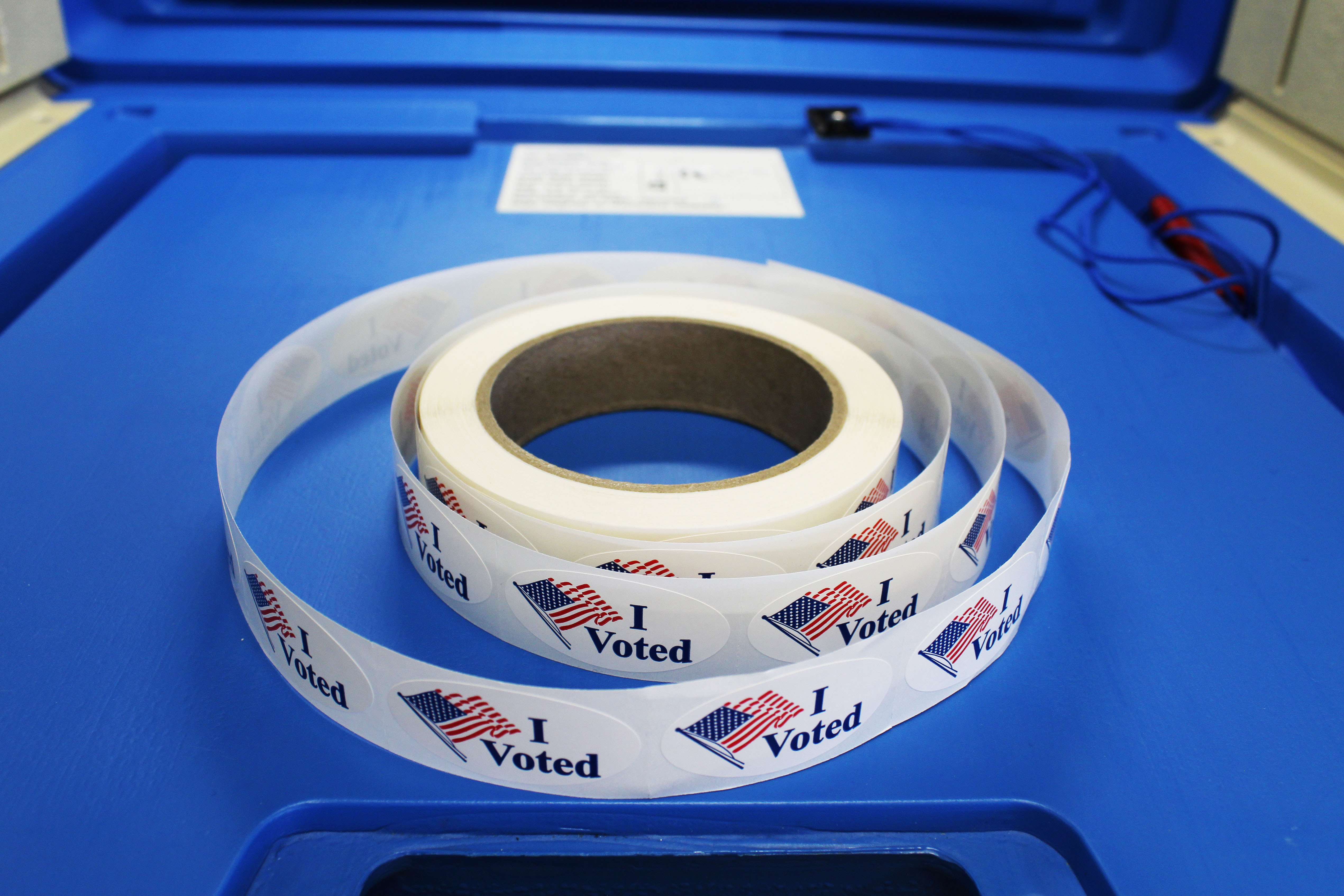 """A roll of """"I voted"""" stickers designed with the American flag is placed on the writing surface of a blue voting booth."""