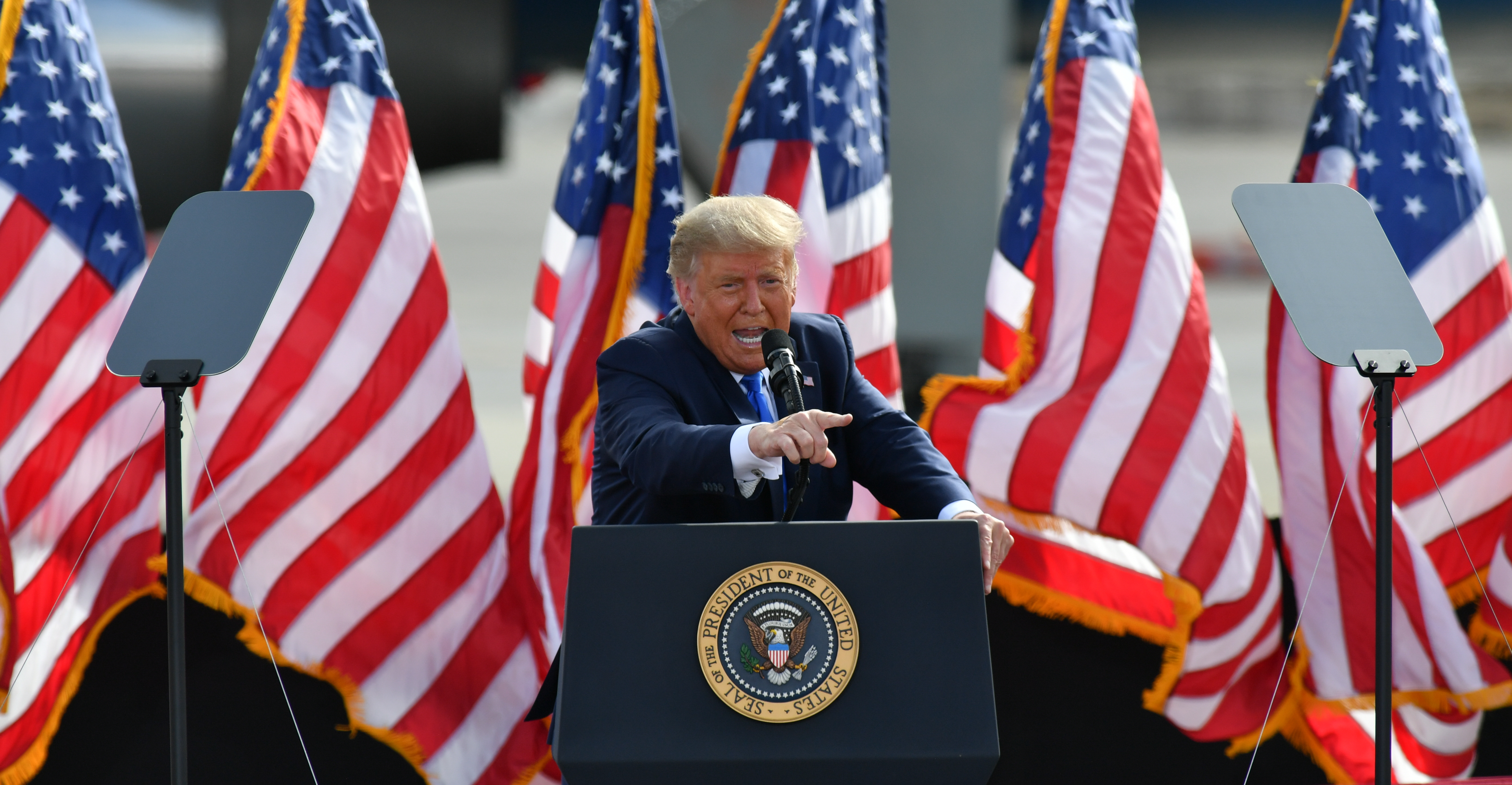 President Trump speaking and pointing from a podium backed by US flags.