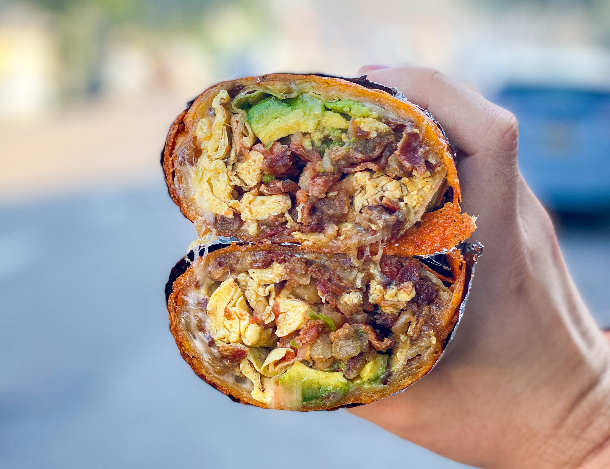 A split open breakfast burrito showing its innards, with a cheese wrap on the outside.