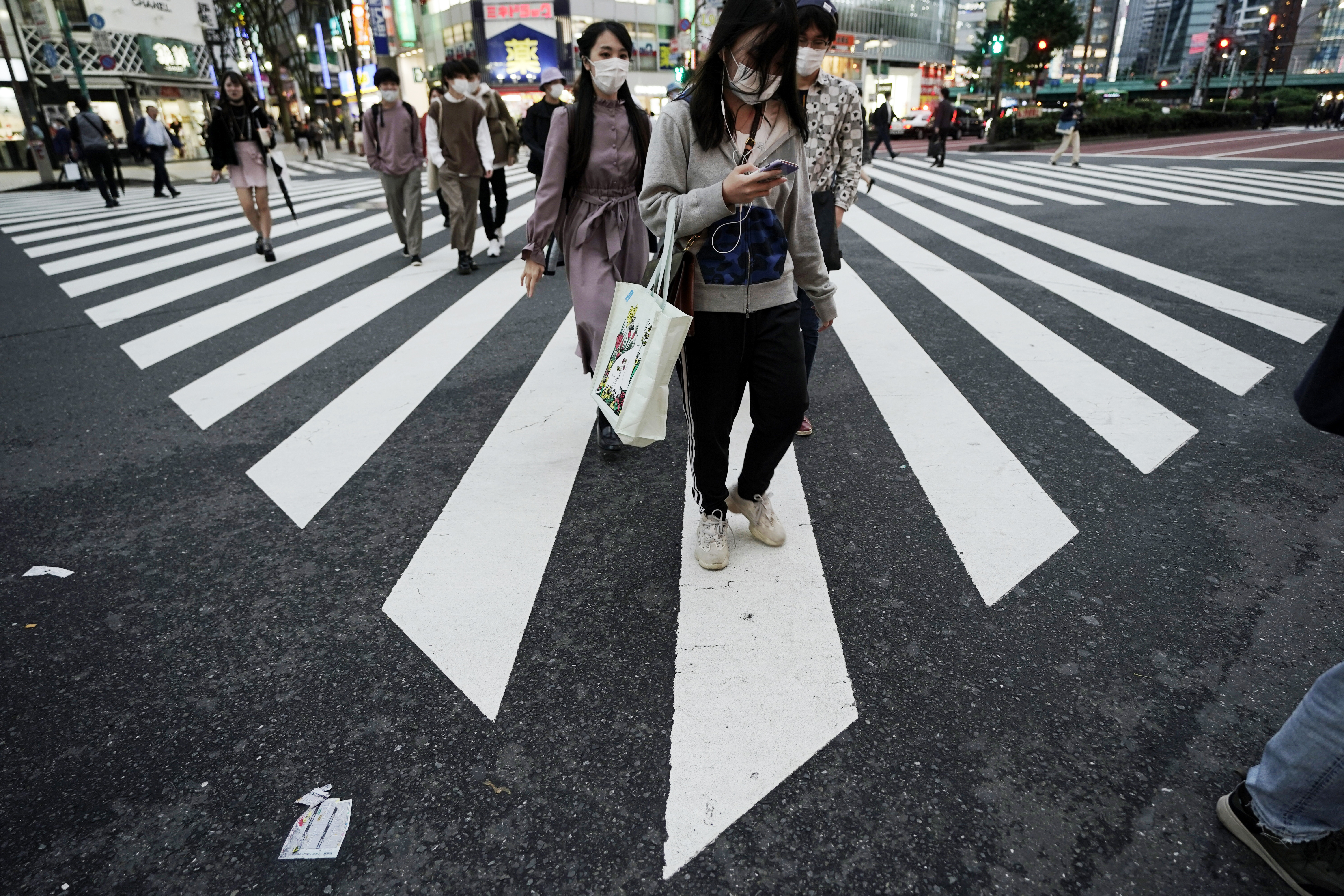 People wearing protective masks to help curb the spread of the coronavirus walk at a a pedestrian crossing Thursday, Oct. 15, 2020, in Tokyo. The Japanese capital confirmed more than 280 new coronavirus cases on Thursday.