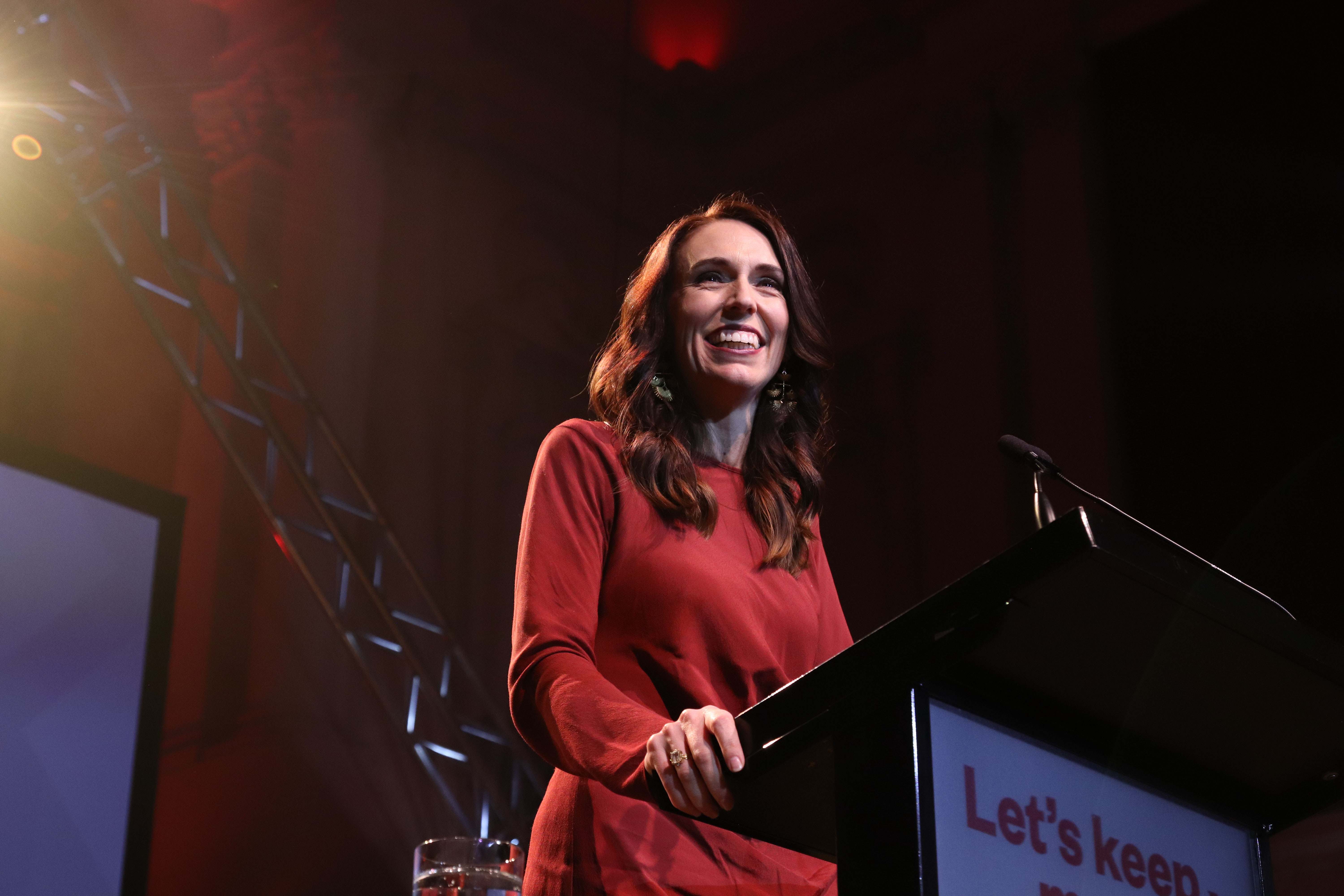 Jacinda Ardern smiles while speaking at a podium.