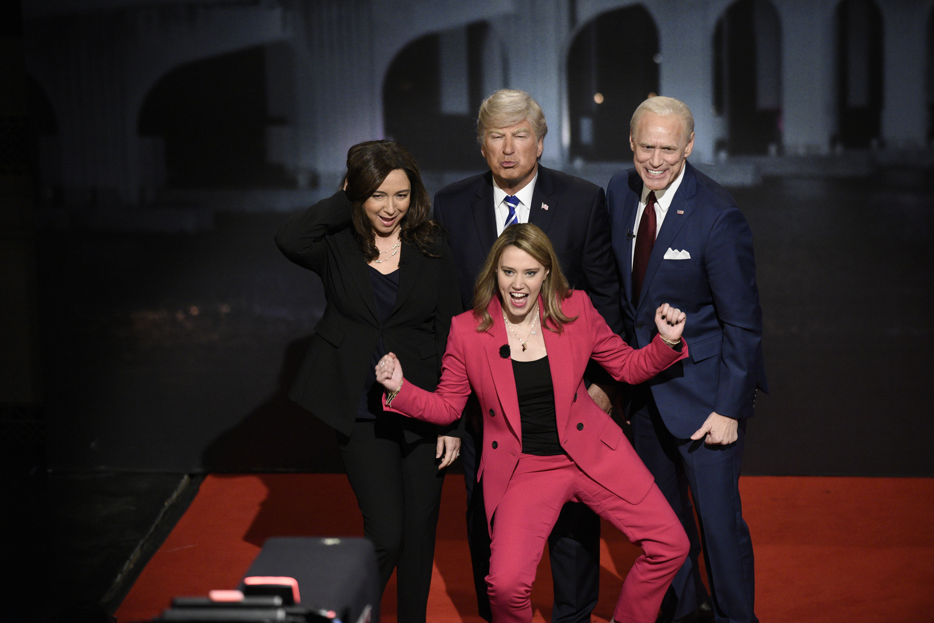 "Maya Rudolph, Alec Baldwin, Jim Carrey, and Kate McKinnon stand together dressed as Sen. Kamala Harris, President Donald Trump, Democratic nominee Joe Biden, and NBC's Savannah Guthrie. All the ""politicians"" have on dark suits; Baldwin is pouting, Carrey smiling broadly. McKinnon, in a pink suit, shouts, her arms raised."