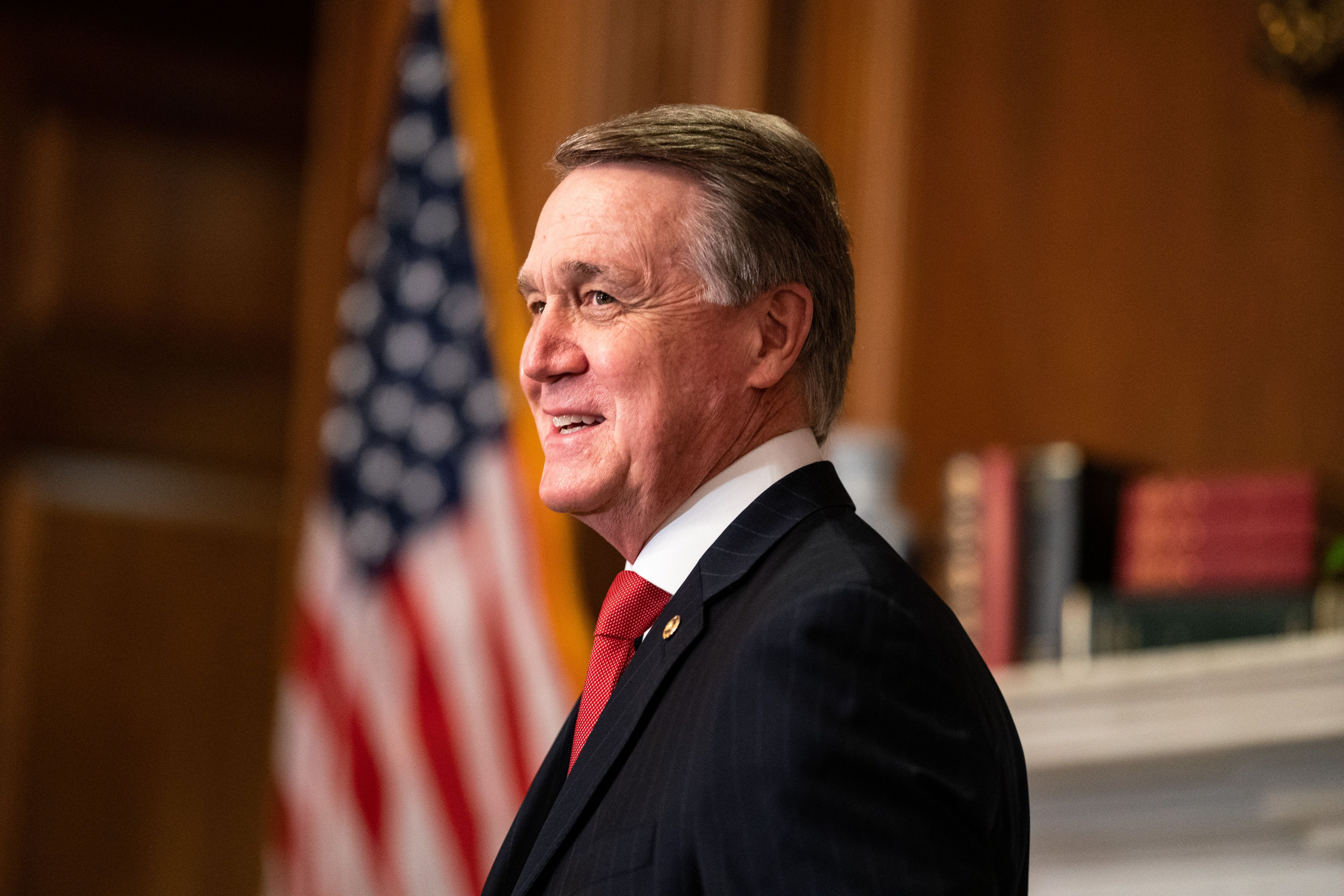 An older white man, Sen. David Perdue, in a black suit and red tie, stands smiling in front of a US flag.