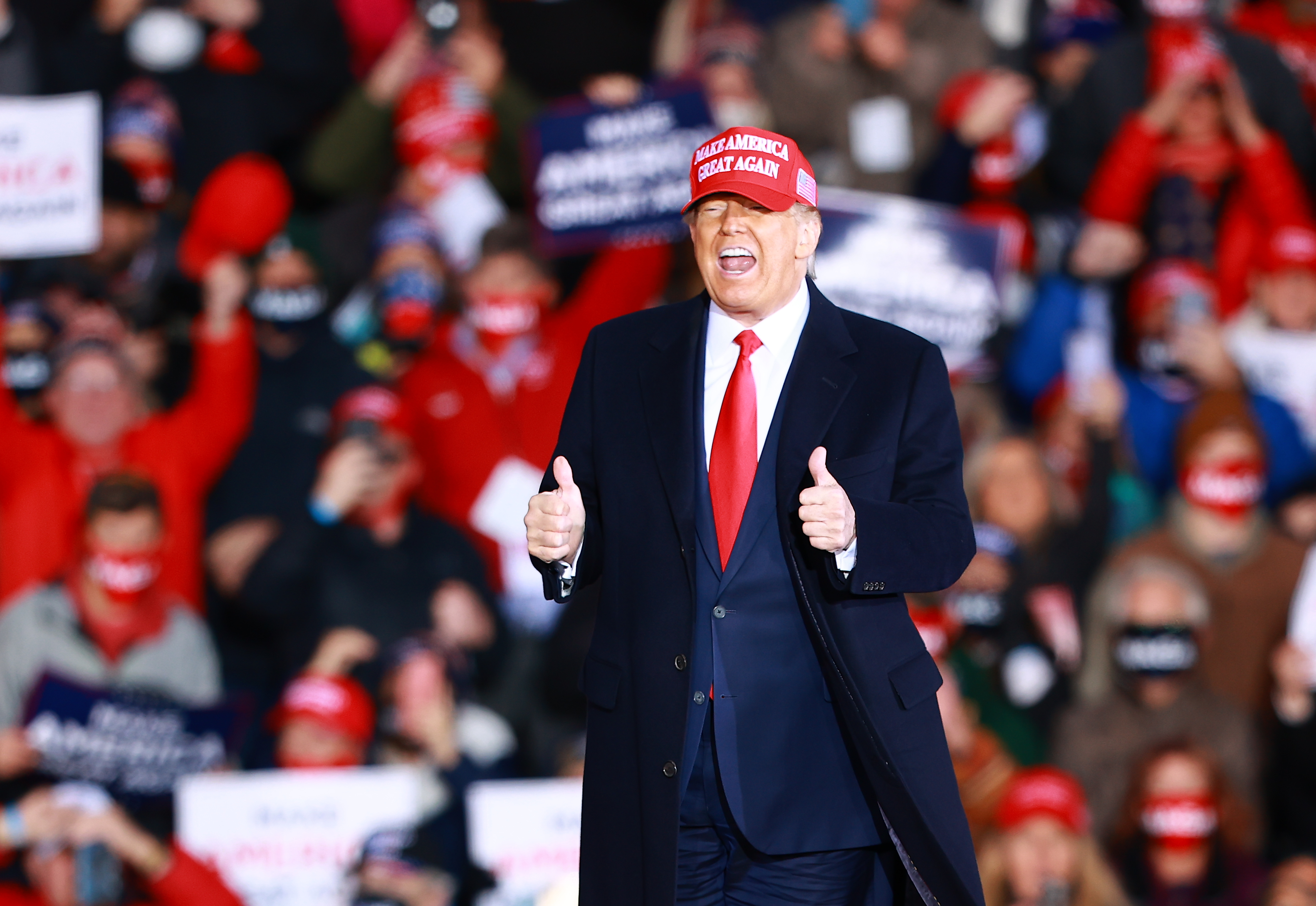 President Trump, gesturing and speaking, wears a red MAGA hat, a navy blue suit, and a dark overcoat in front of a crowd of his supporters.