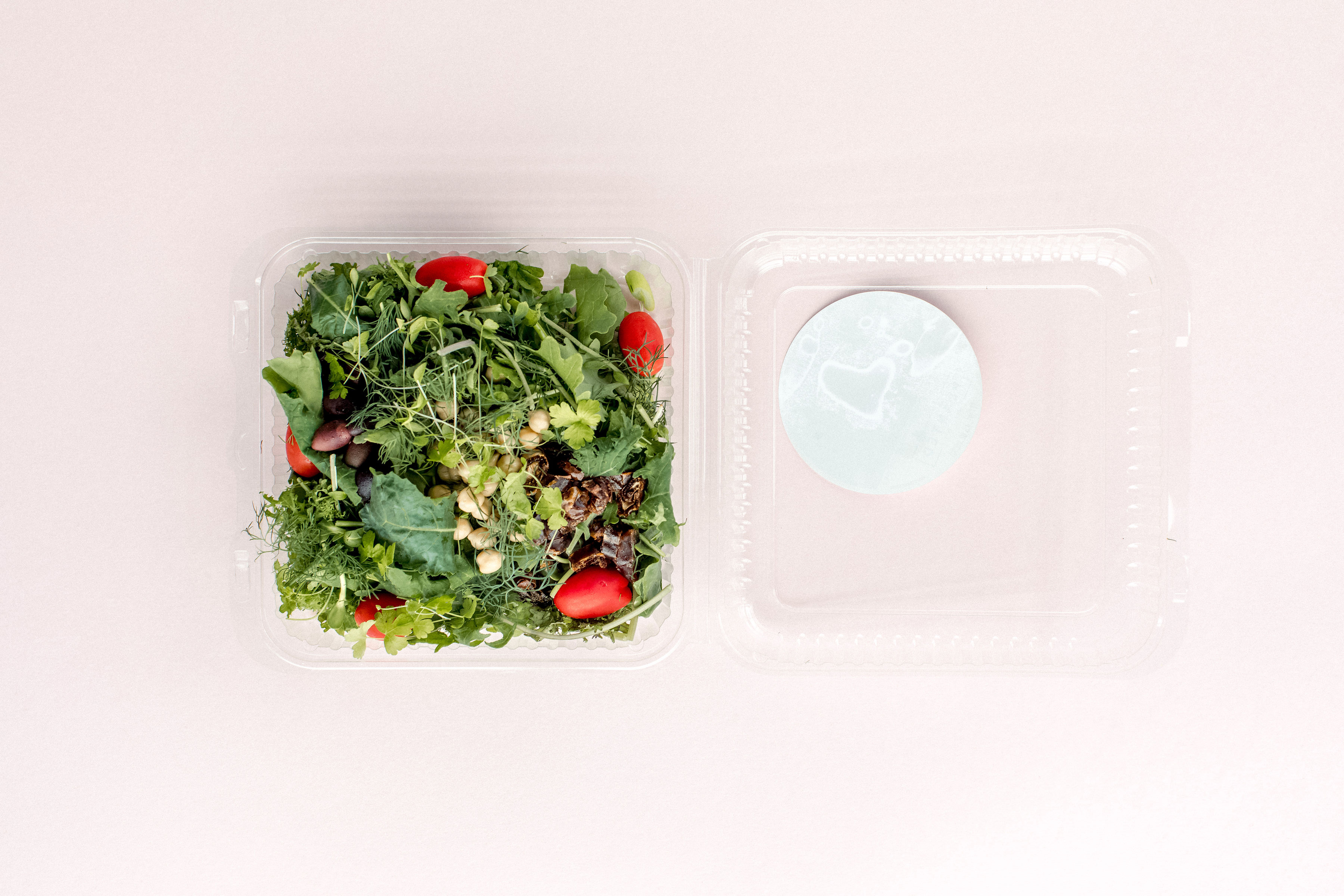 The Moroccan salad from Planted Detroit sits in a plastic container on a light pink background. It has tomatoes, greens, olives, and chickpeas.