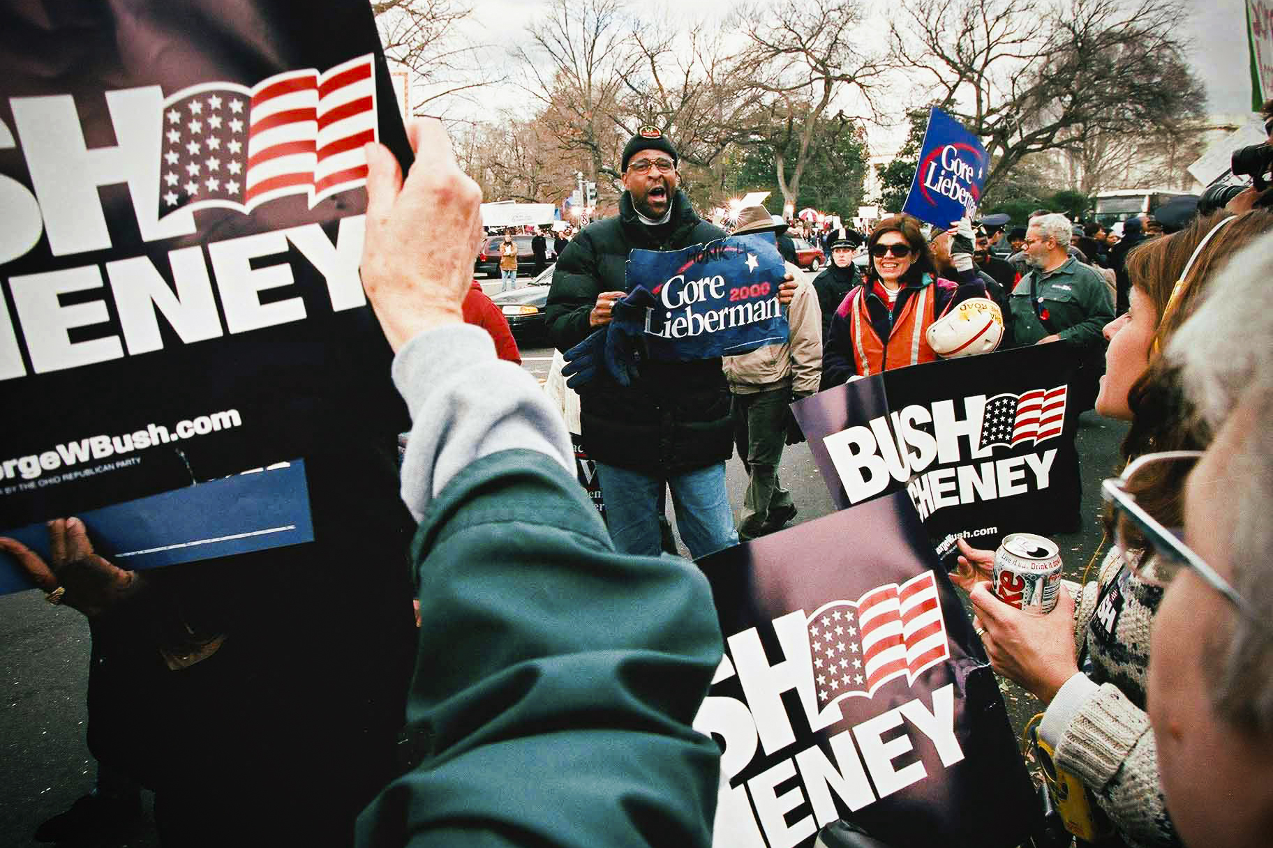 Two groups of people, one holding Bush/Cheney campaign signs, the other with Gore/Lieberman campaign signs, both chanting at each other outside the US Supreme Court.