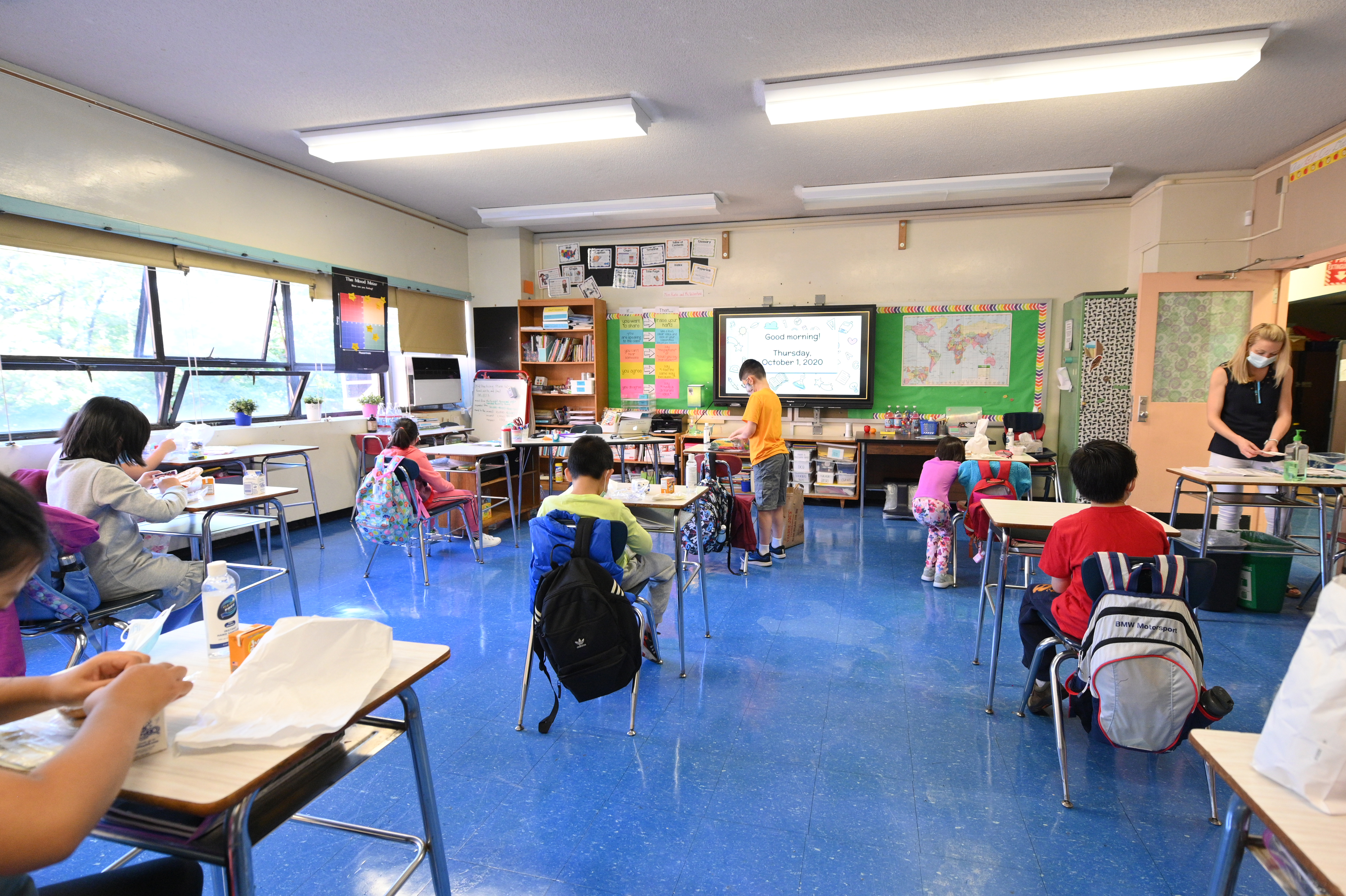 Children sit in a classroom with desks spaced six feet apart. A teacher wearing a mask stands at the front.