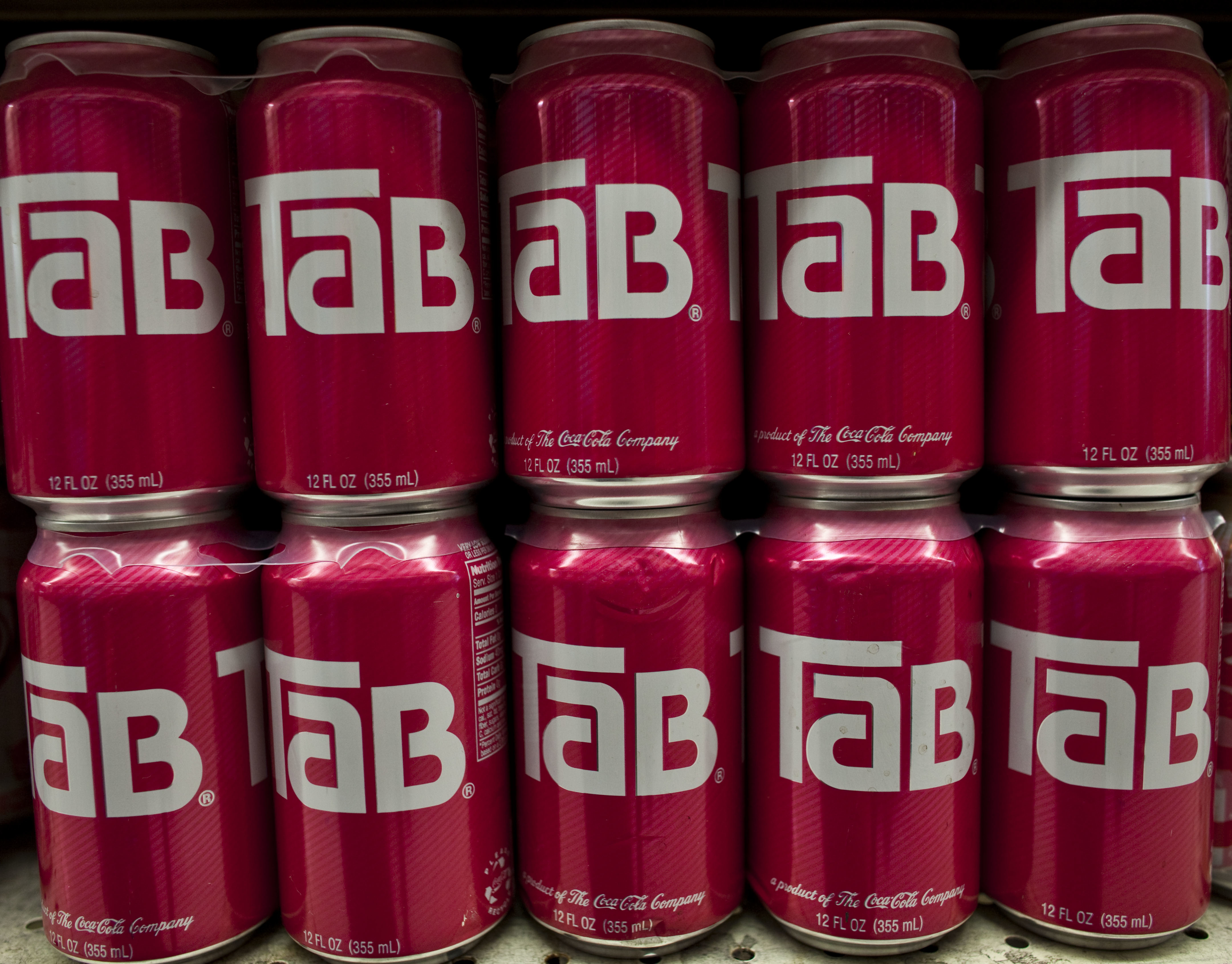 Rows of Tab soda cans displayed on a grocery shelf.