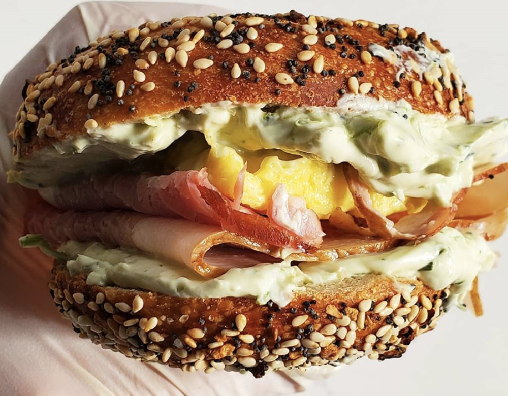 Sideview of scrambled eggs, ham, and tarragon cream cheese on a bagel at Porkchop & Co.