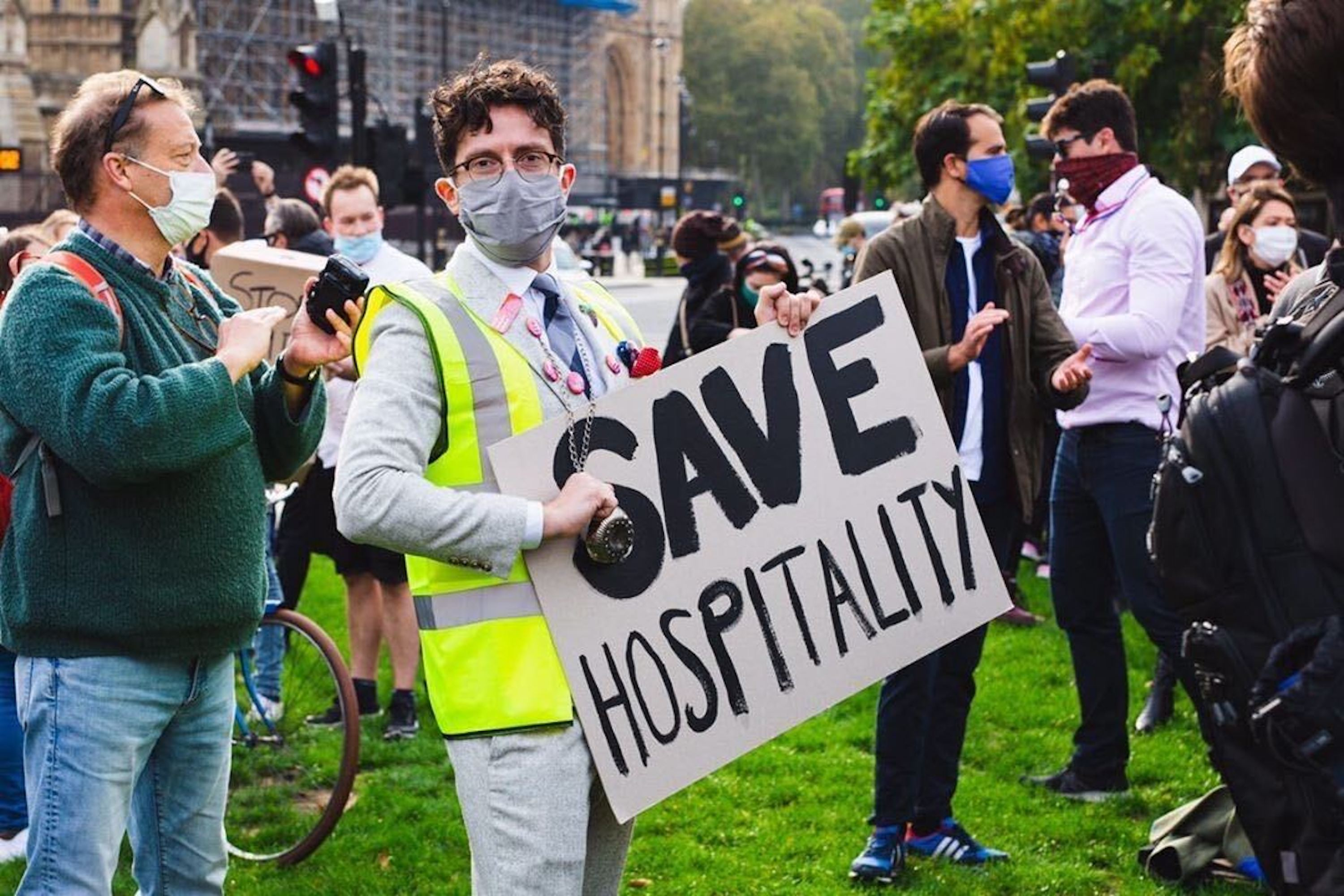 """A protester wearing a mask and a hi-vis jacket holds up a placard that reads """"save hospitality,"""" in capital letters, at Parliament Square in London. He is surrounded by fellow protesters, also in masks"""