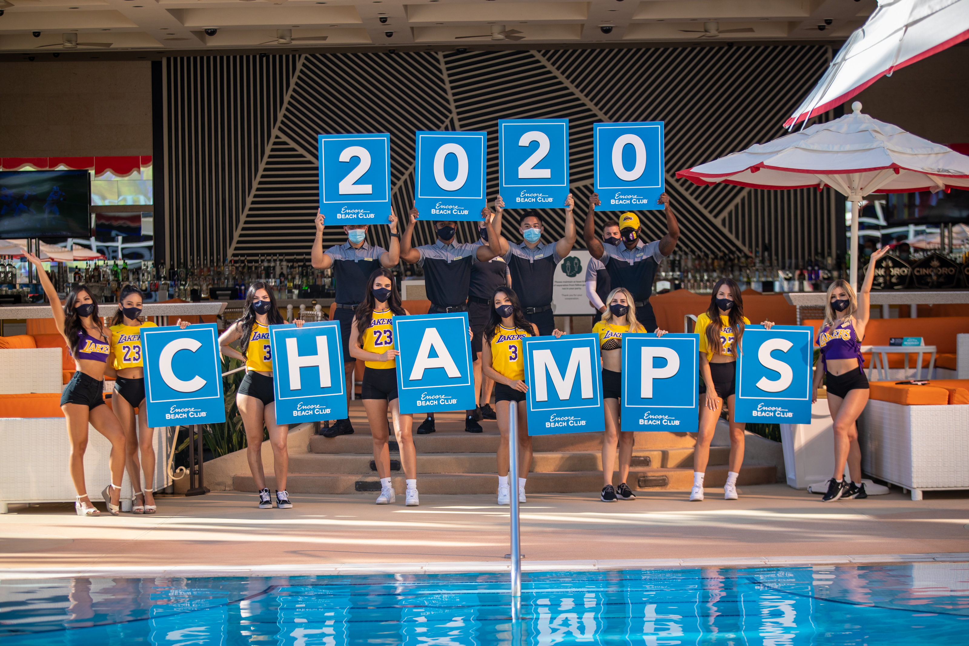"""Women wearing Los Angeles Lakers attire hold numbers and letters that say """"2020 Champs"""""""
