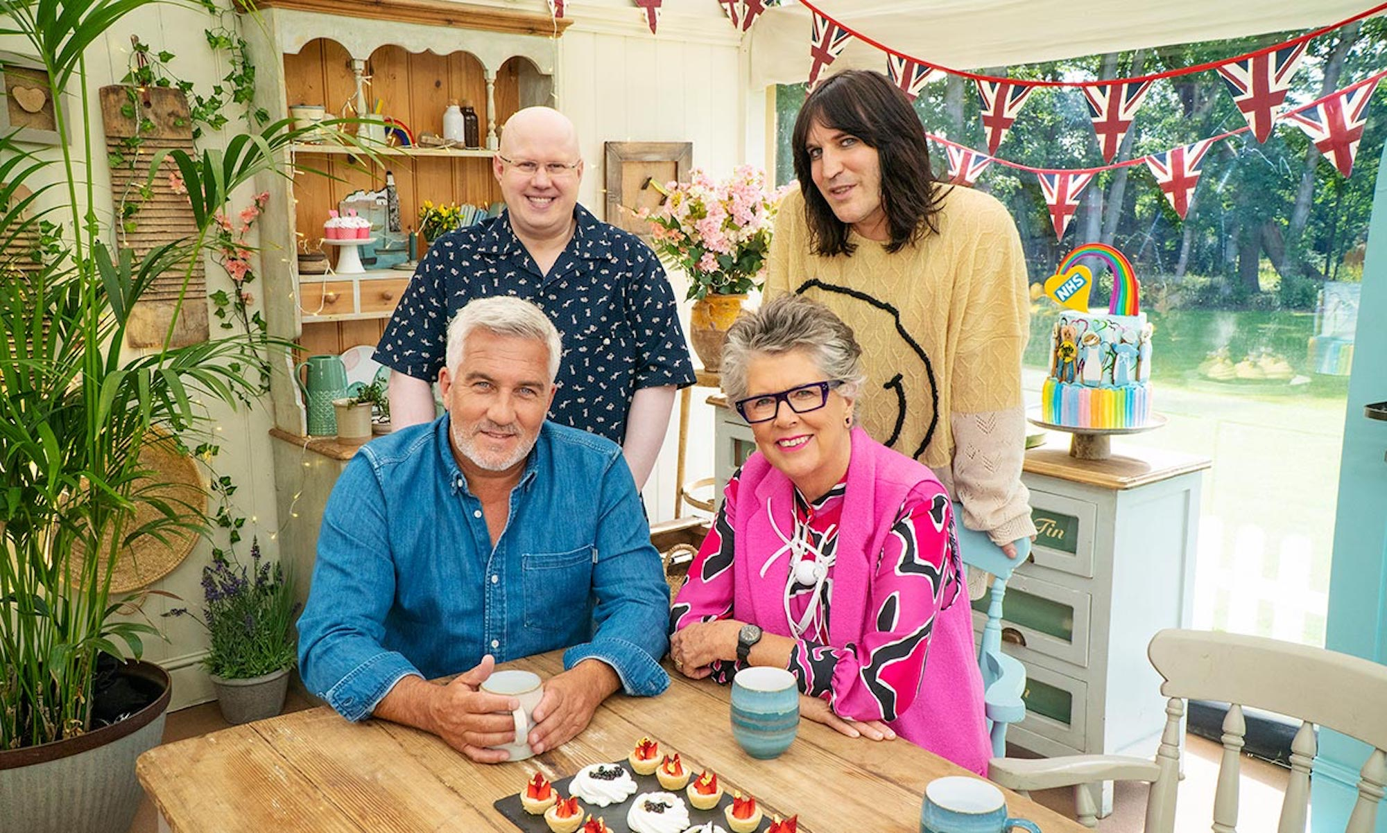 "The hosts and judges of ""The Great British Bake Off"" gather around a light wood table with a china hutch and Union Jack bunting in the background."