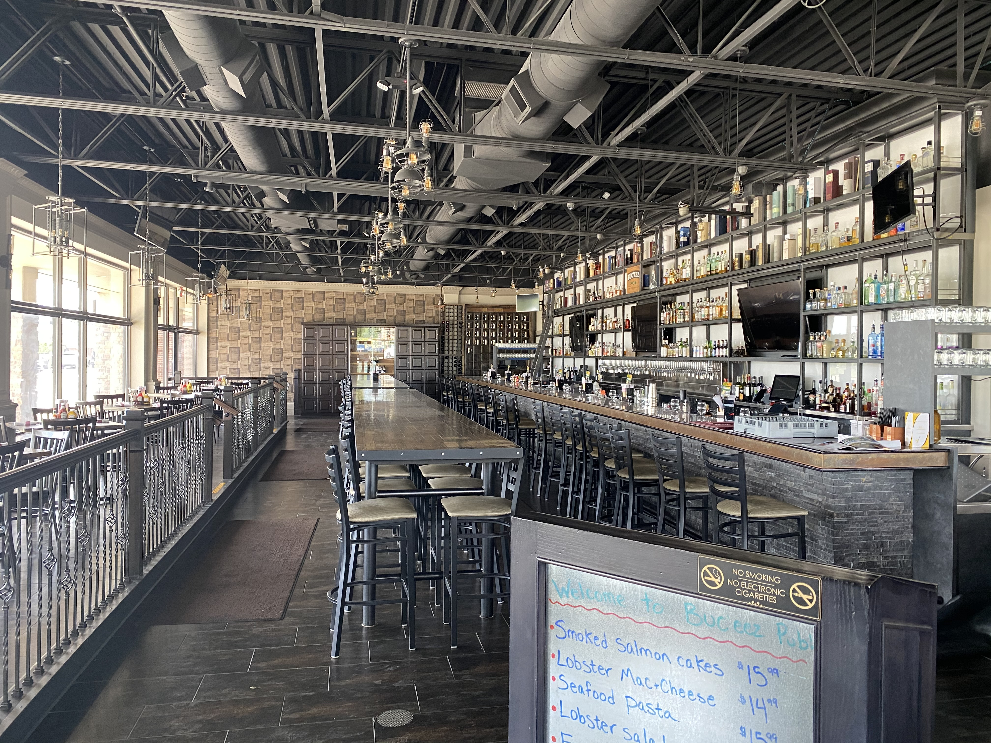 An empty bar interior with a long, stone-tiled bar and industrial ceilings with exposed ventilation.
