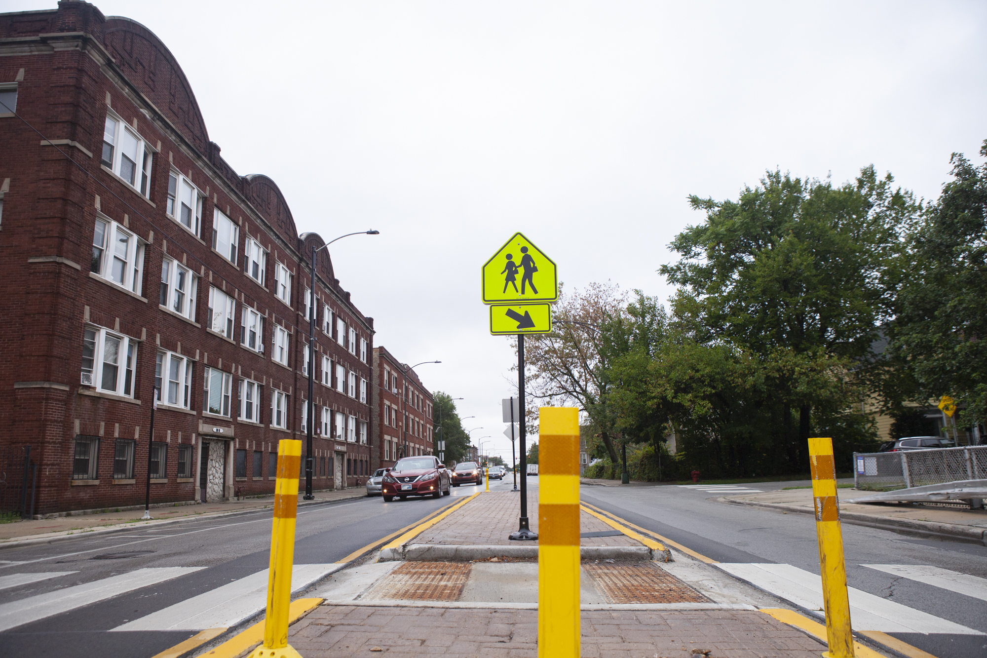 A school crossing sign in a cross walk.