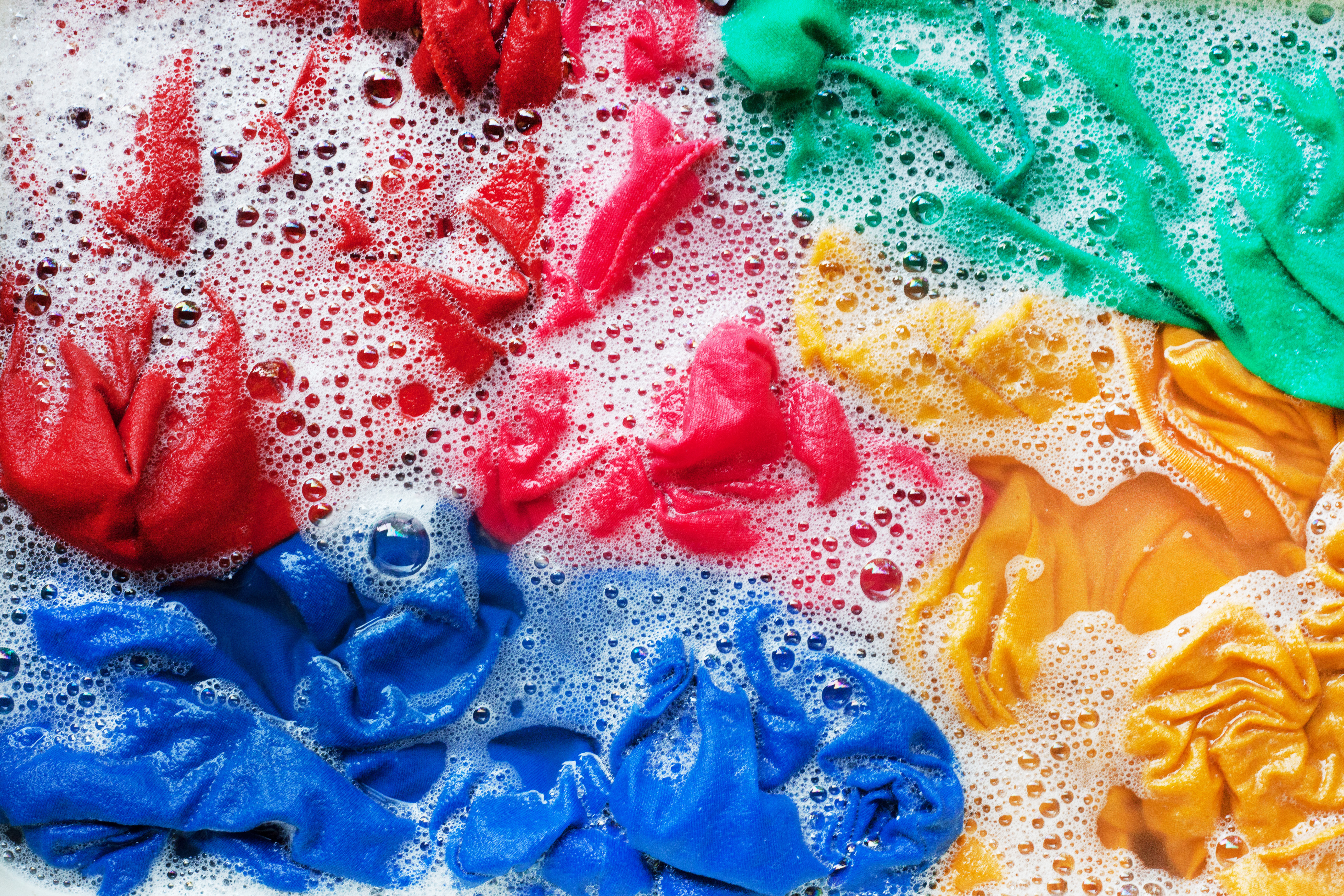 red, blue, yellow, and green items of clothing submerged in water and suds