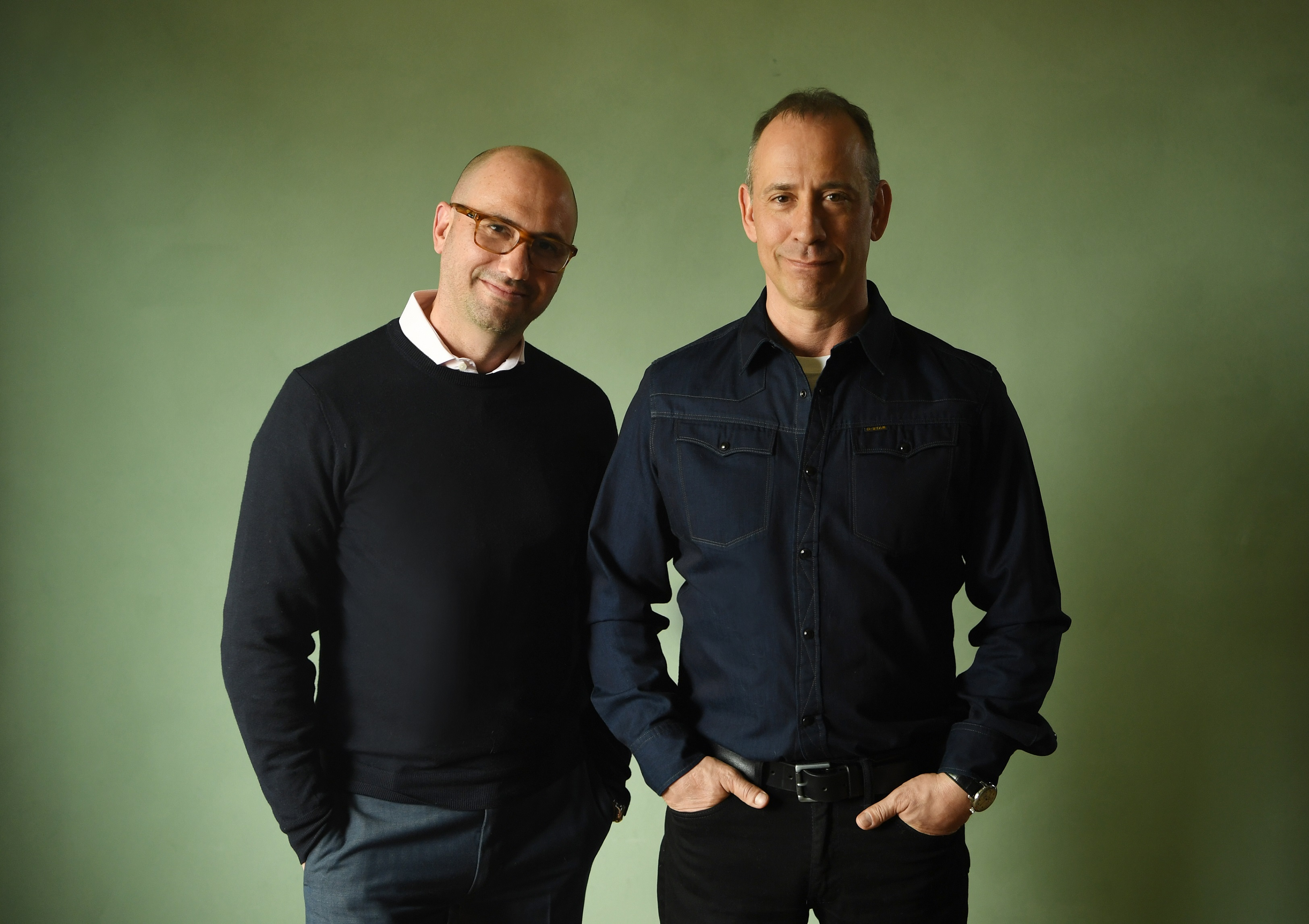 Two men wearing black stand in front of a green background