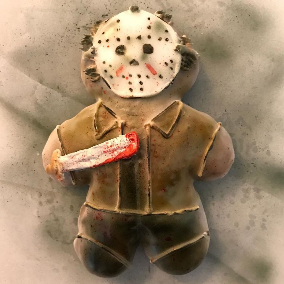 A doughnut shaped and decorated like Jason Voorhees of Friday the 13th, complete with bloody machete
