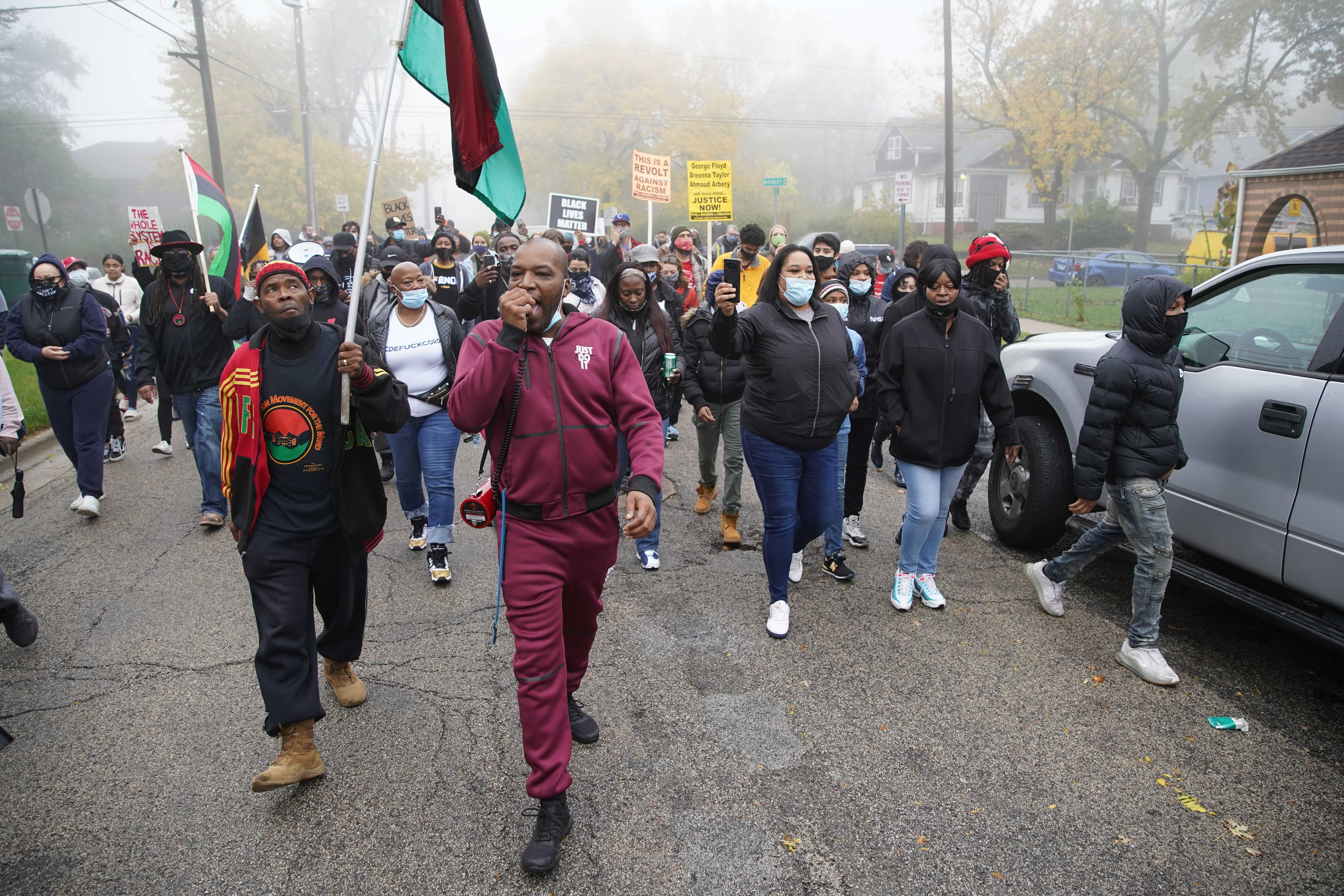 Rayon Edwards leads a chant and march during rally and protest against police brutality Thursday after Marcellis Stinnettte, 19, was fatality shot by police in Waukegan.