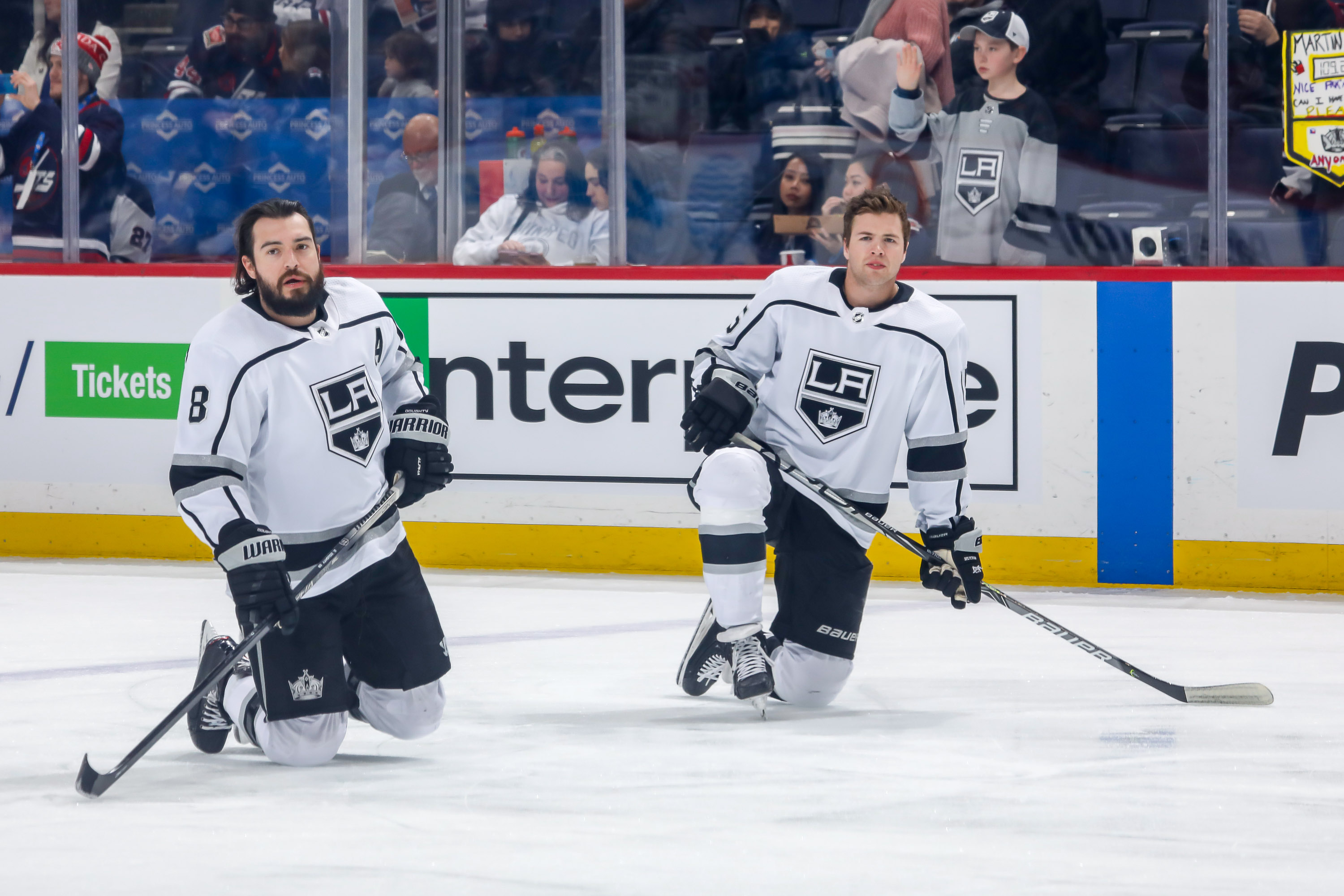 Drew Doughty #8 and Ben Hutton #15 of the Los Angeles Kings take part in the pre-game warm up prior to NHL action against the Winnipeg Jets at the Bell MTS Place on February 18, 2020 in Winnipeg, Manitoba, Canada.