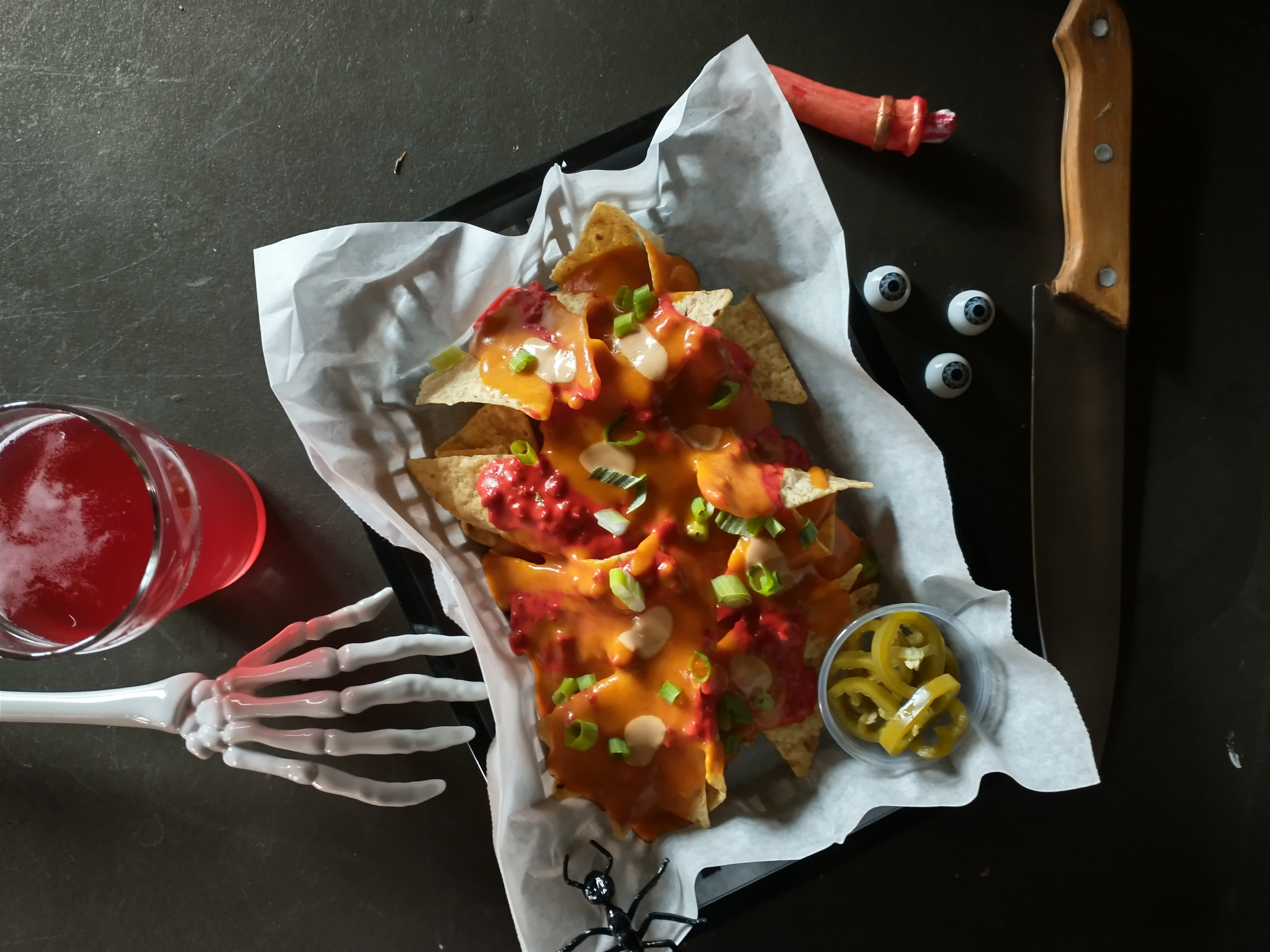 A plastic skeleton arm reaches for a basket of nachos covered in cheese and pickled jalapenos with three googly eyes beside the basket and large knife for Halloween