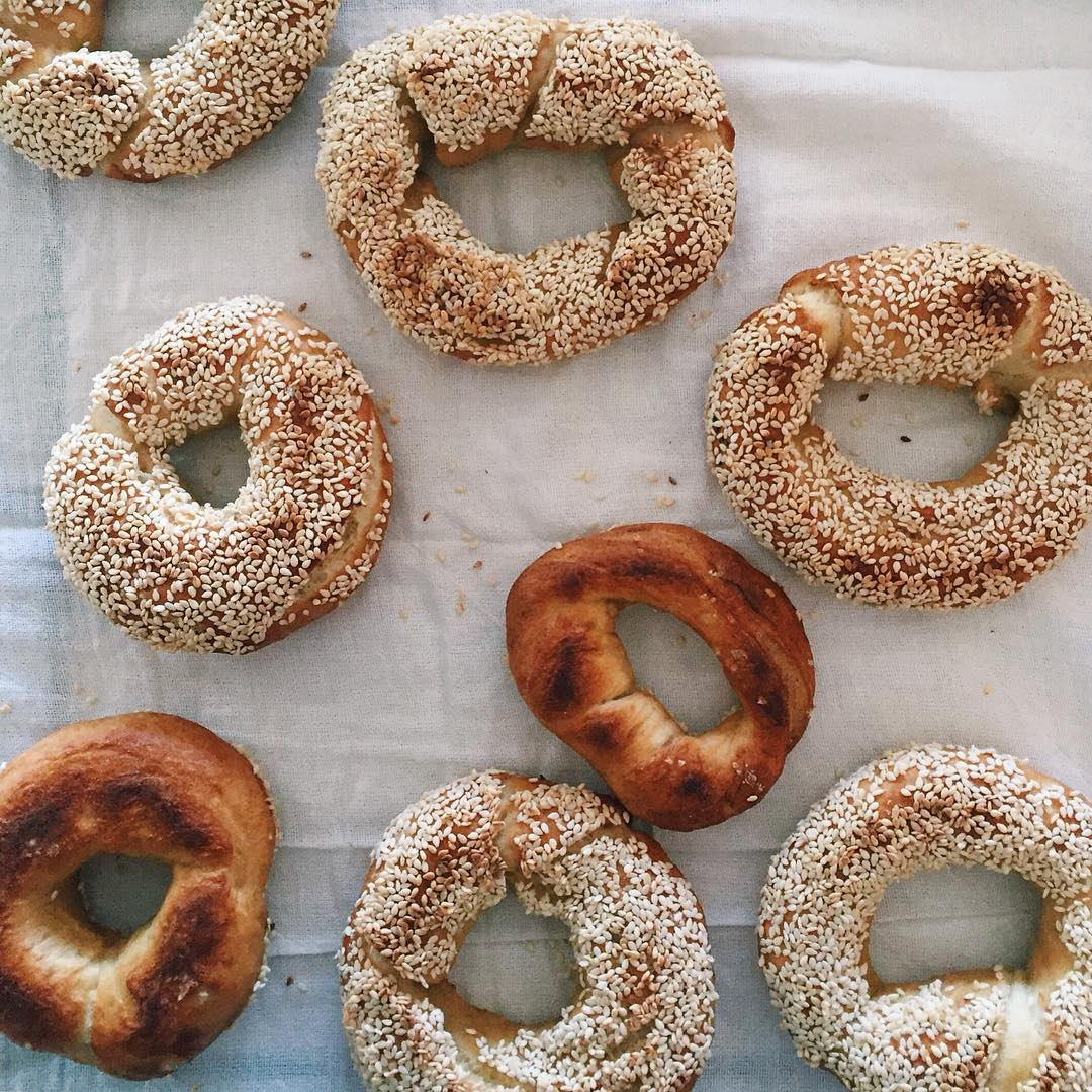 A top-down look at some loose Montreal-style bagels fresh from an oven, sitting on linen.