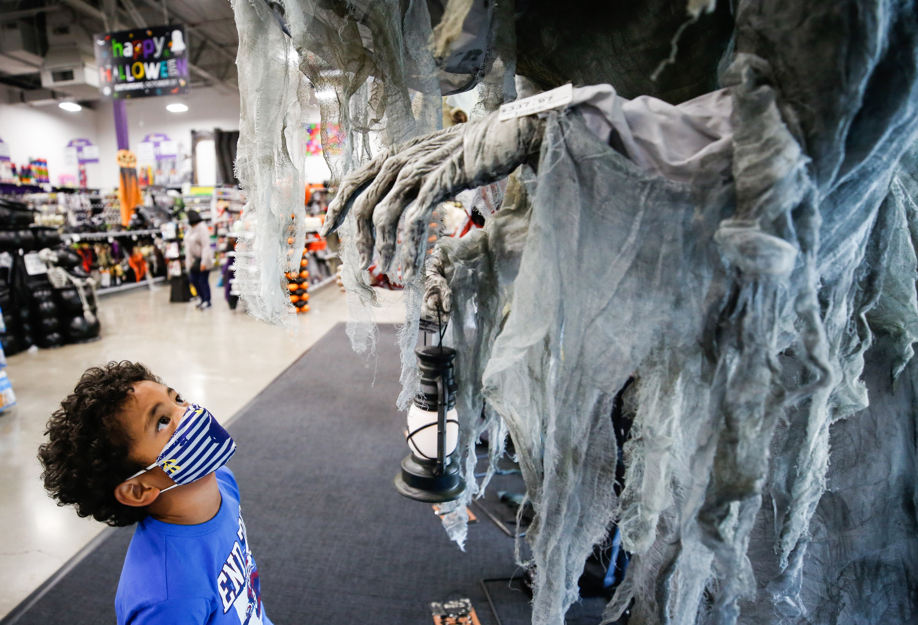 Shane Manu, 6, looks at a Halloween decoration at Zurchers, a costume and party supply store, in Salt Lake City on Friday, Oct. 16, 2020.