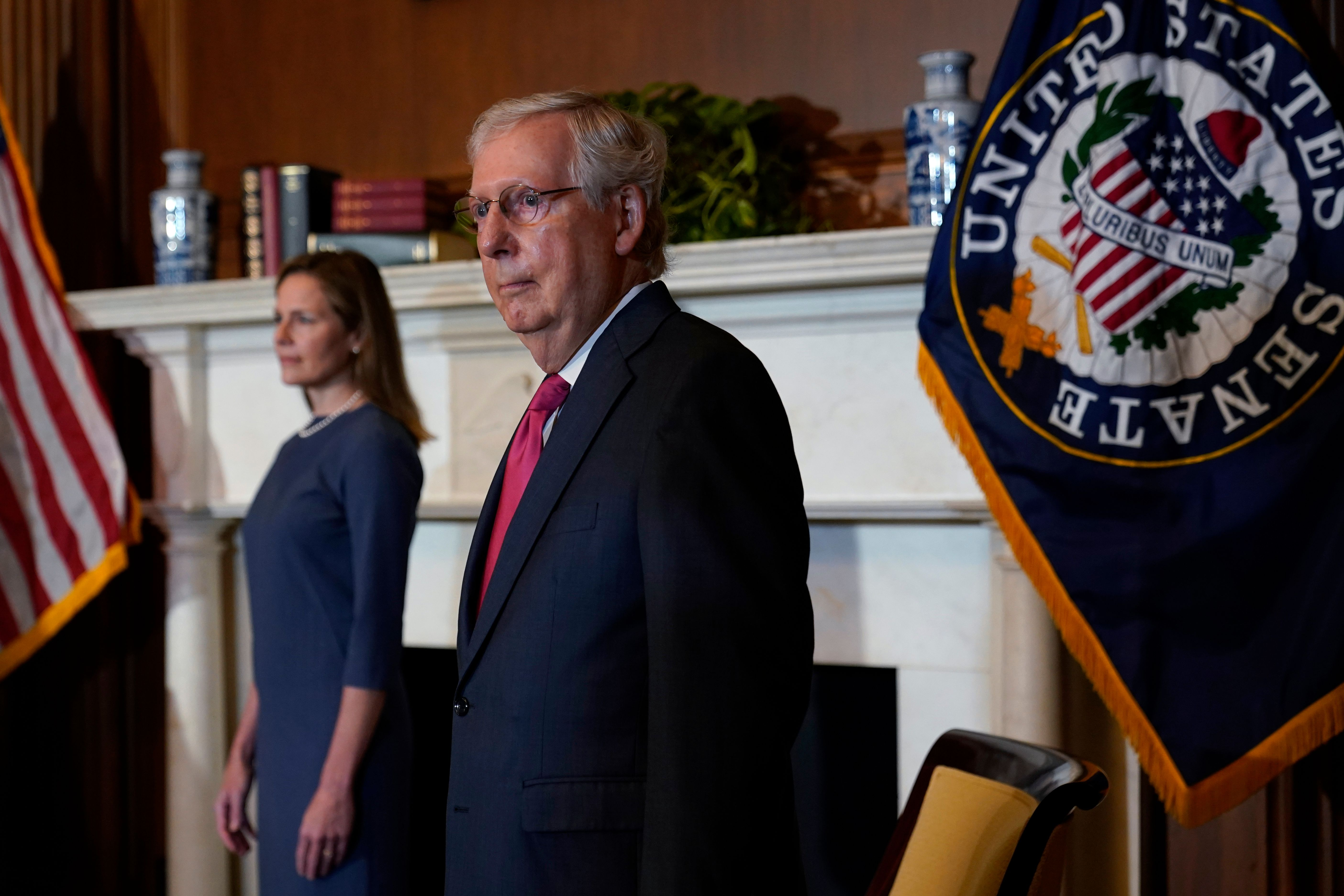 "McConnell, in a blue suit and red tie, wears a neutral expression as he stands before a gold-trimmed blue flag with an eagle that says ""United States Senate."" On the left is Barrett, in a blue dress."